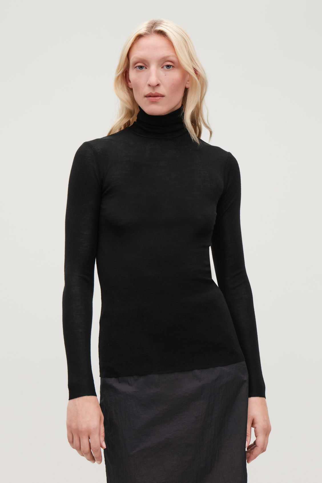 Model side image of Cos roll-neck wool top in black