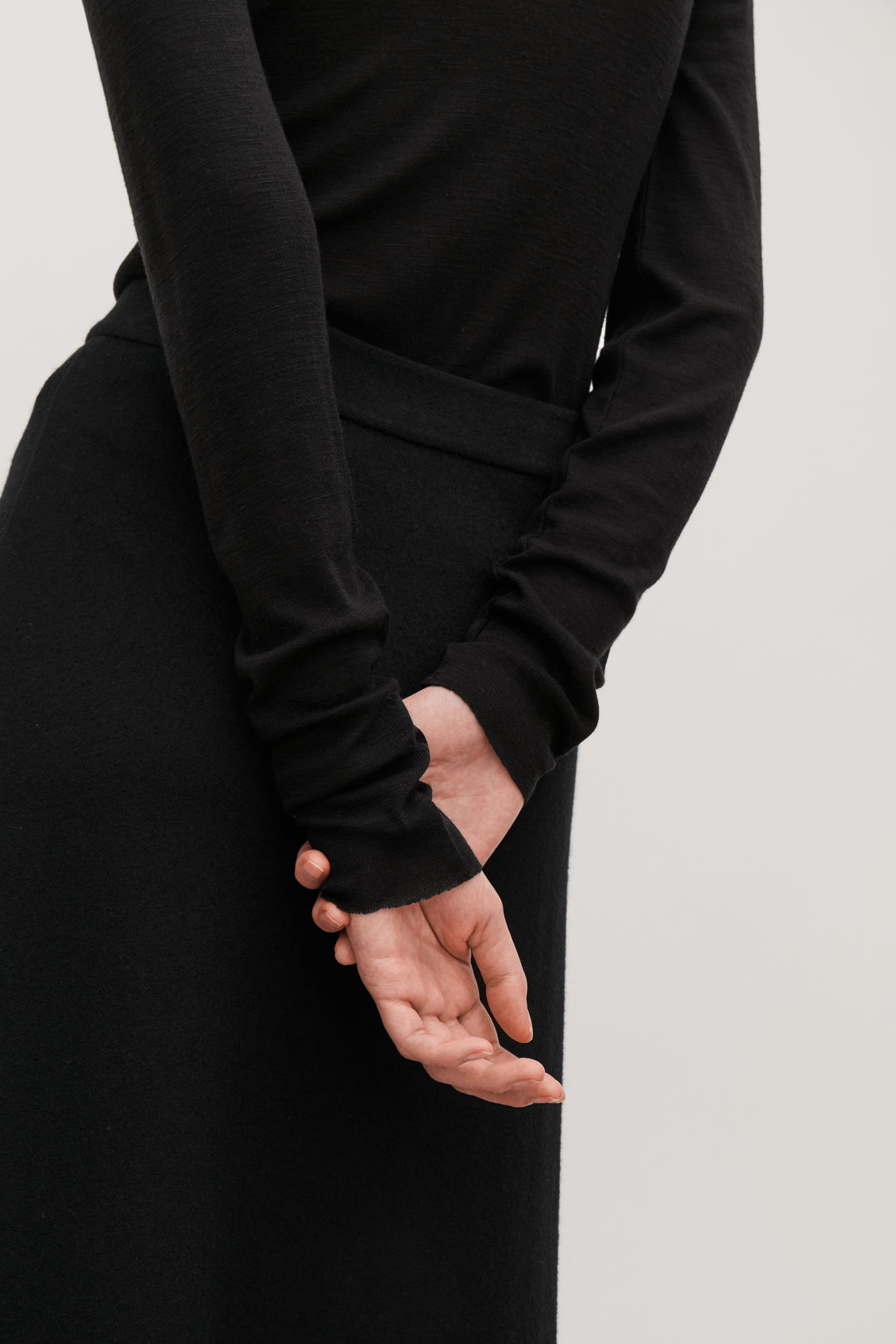 Model side image of Cos fine roll-neck wool top in black