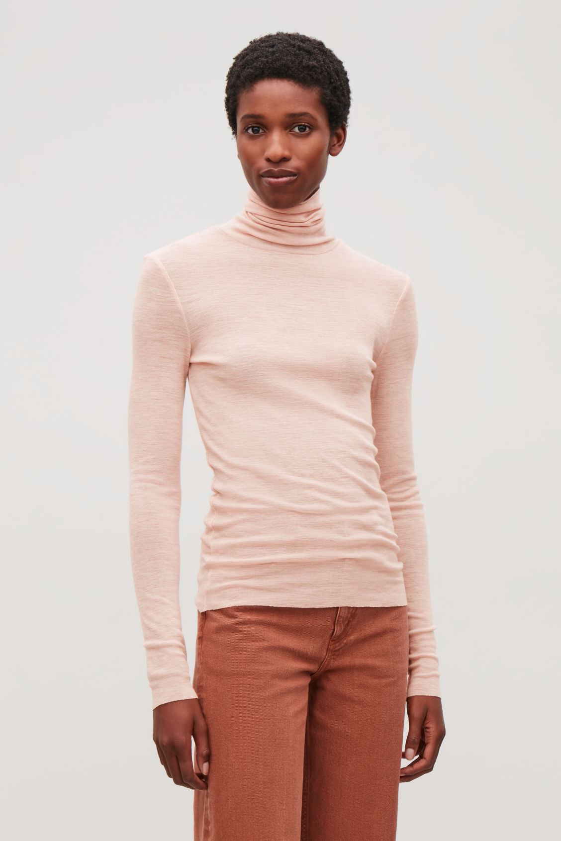 Model side image of Cos fine roll-neck wool top in orange