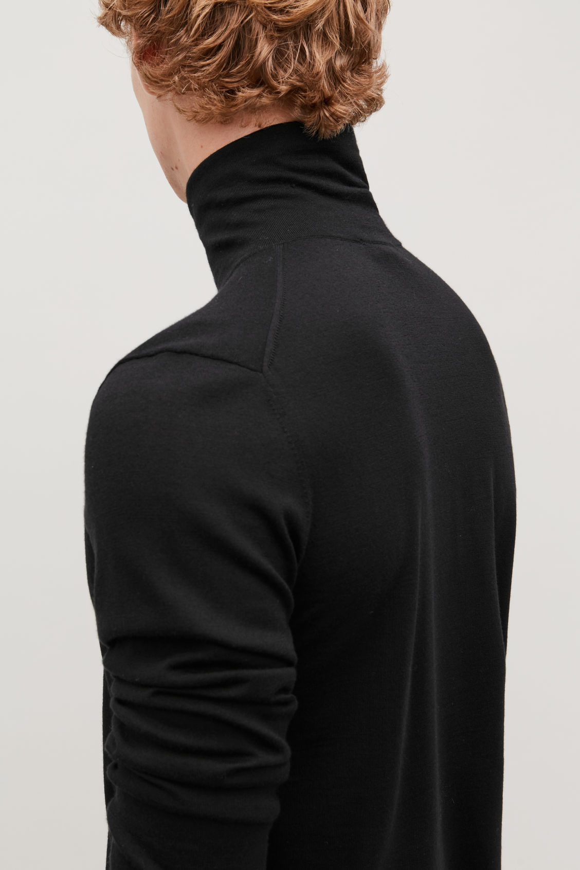 Model side image of Cos merino roll-neck jumper in black