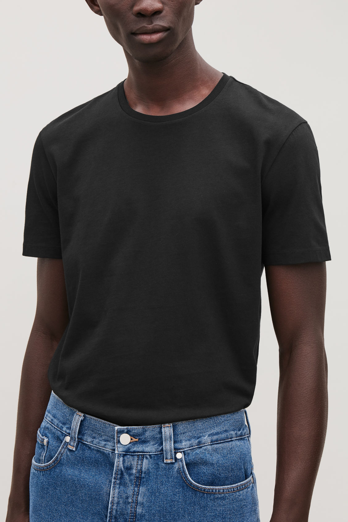 Model side image of Cos round-neck t-shirt in black