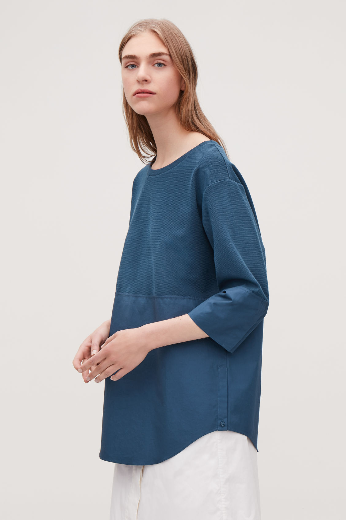 Model side image of Cos sweatshirt with shirt hem in blue