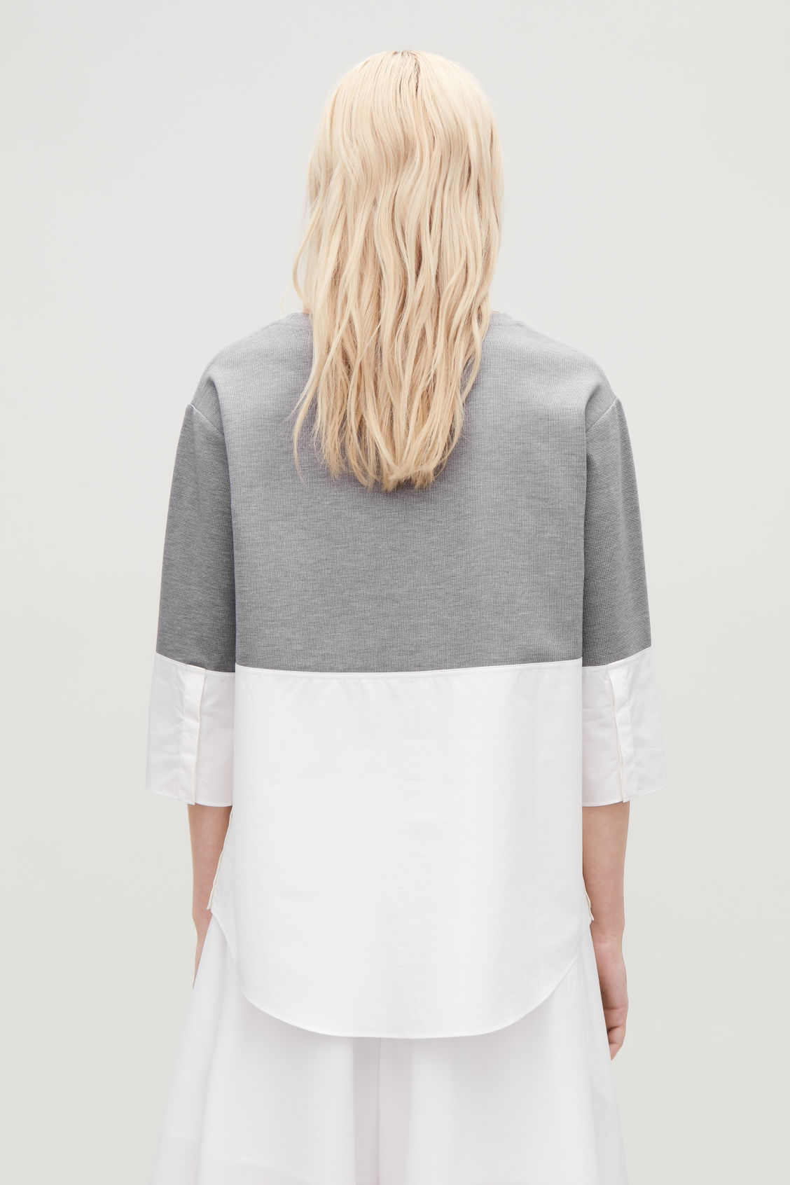 Model side image of Cos jumper with shirt hem in grey