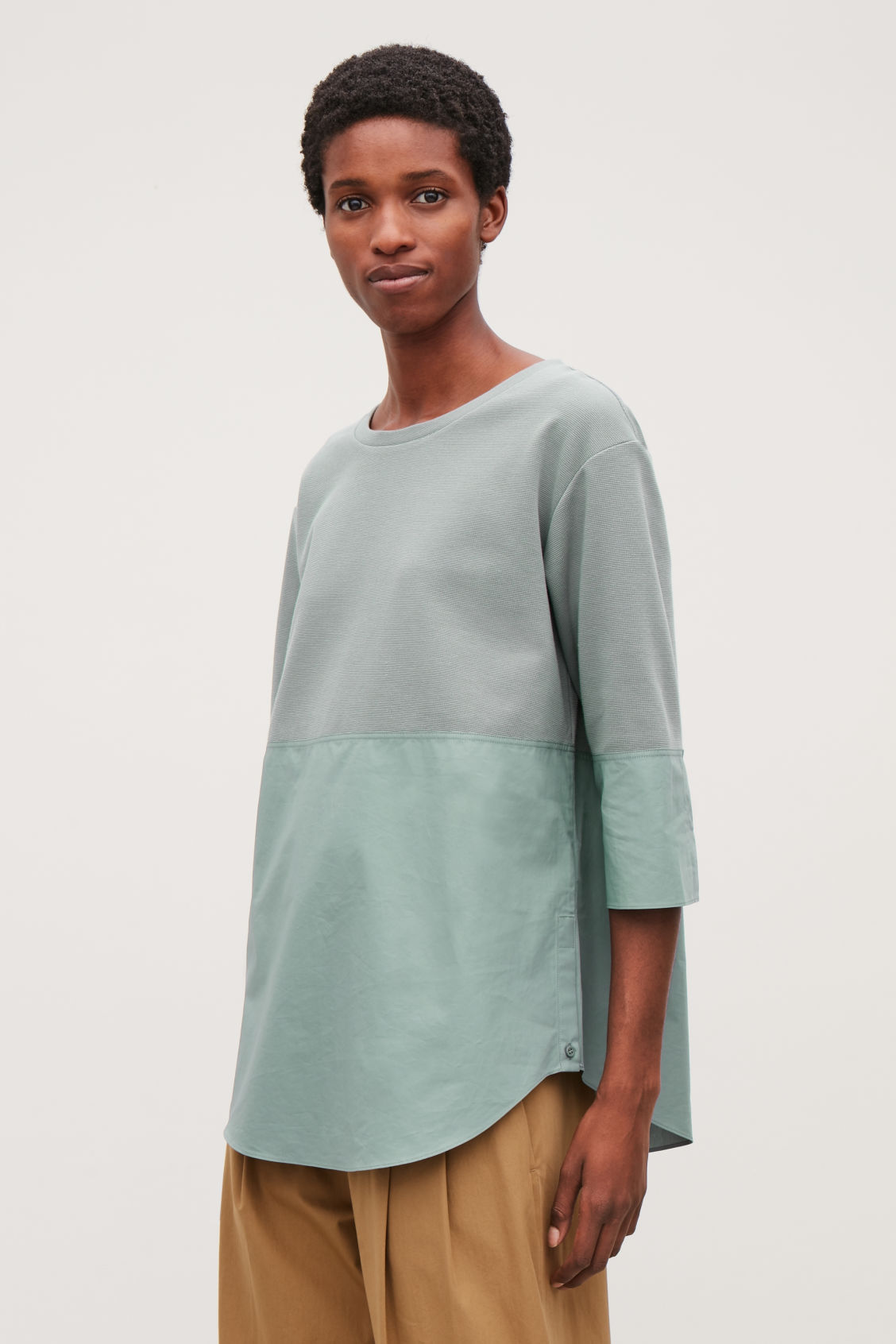 Model side image of Cos sweatshirt with shirt hem in green