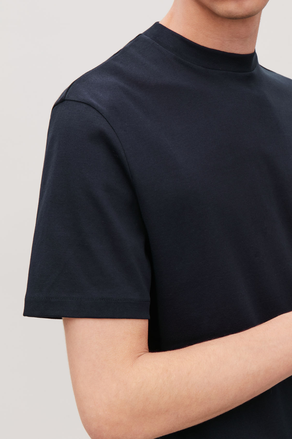 Model side image of Cos t-shirt with raised neck in blue