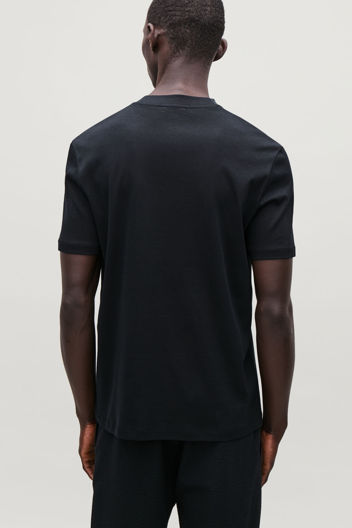 Model side image of Cos t-shirt with mock neck in blue