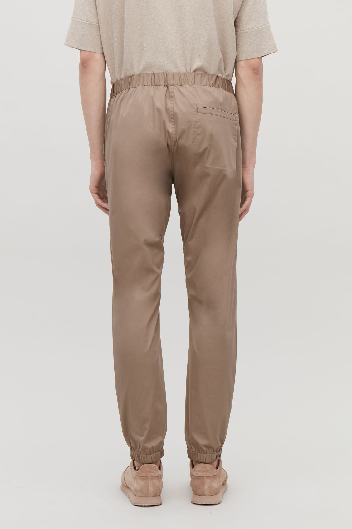 Model side image of Cos elastic-waist cotton trousers in beige