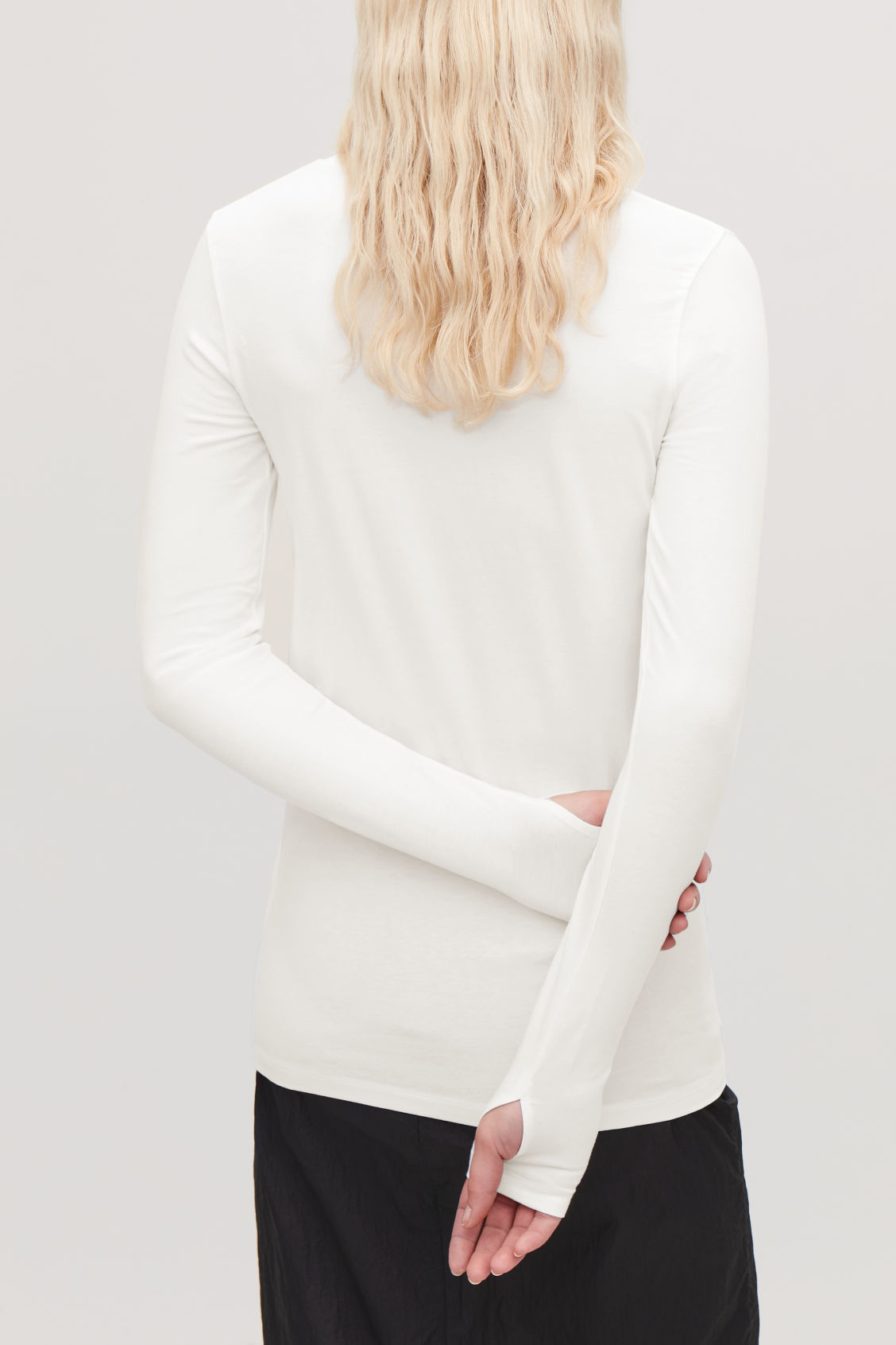 Model side image of Cos slim-fit top with thumbholes in white