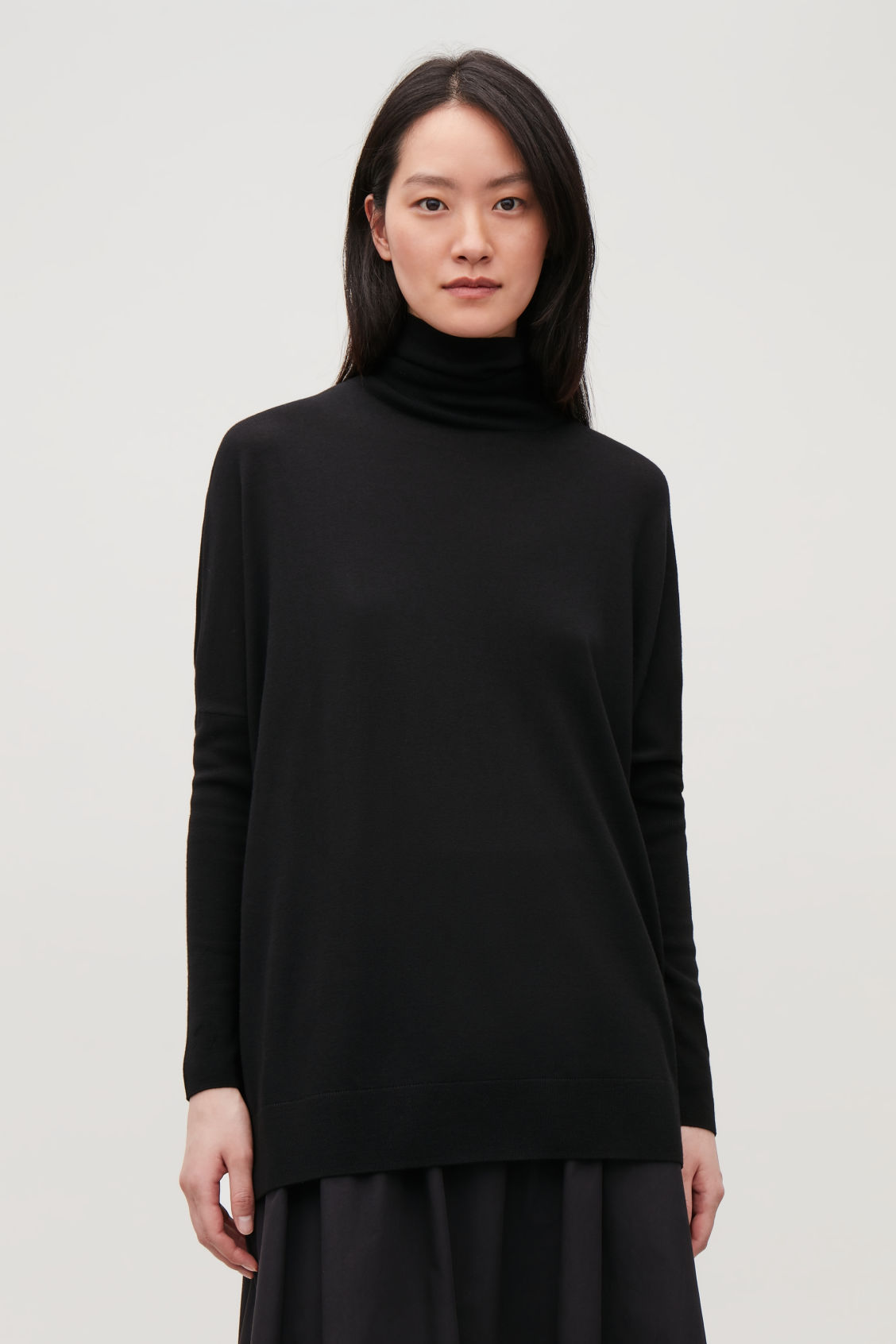 Model side image of Cos roll-neck merino jumper in black