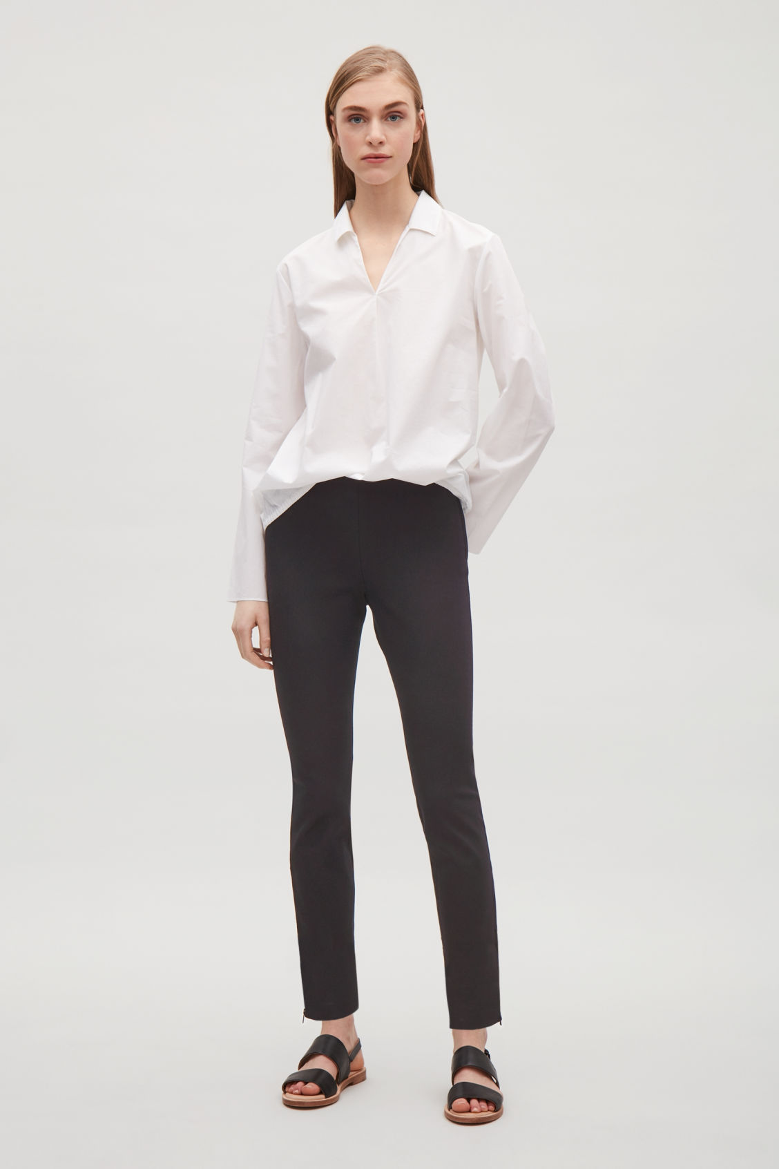 Model front image of Cos slim-fit trousers with ankle zips in black