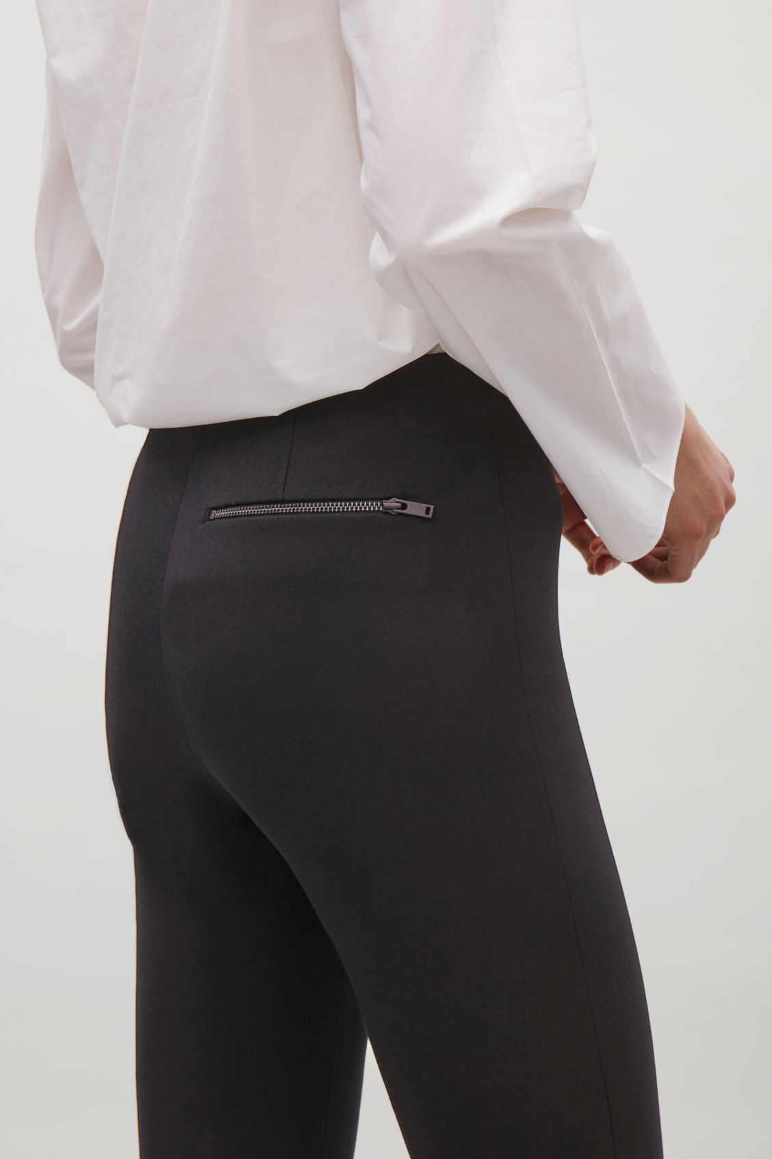 Model side image of Cos slim-fit trousers with ankle zips in black