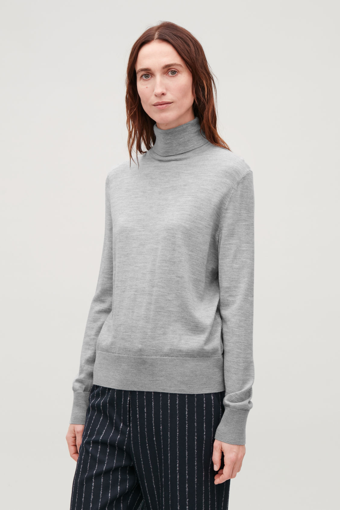 Model side image of Cos roll-neck merino jumper in grey