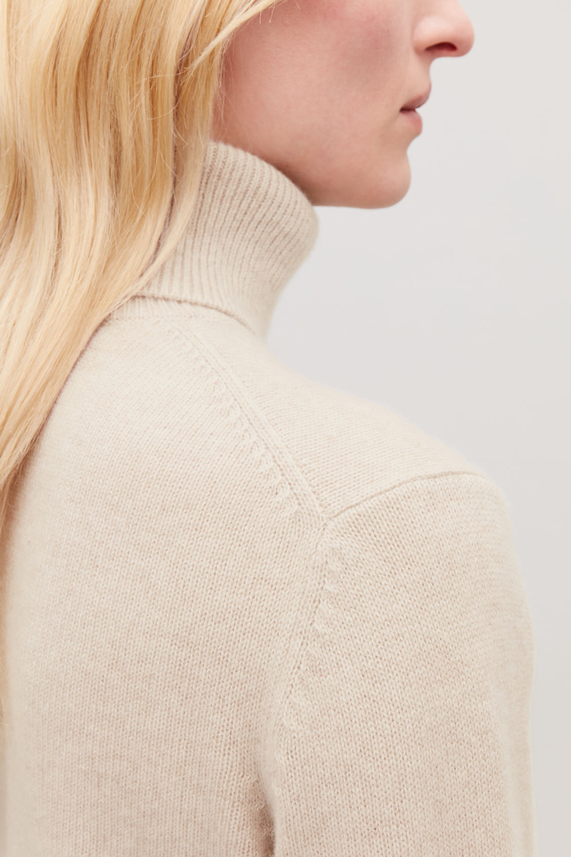Model side image of Cos high-neck cashmere jumper in beige