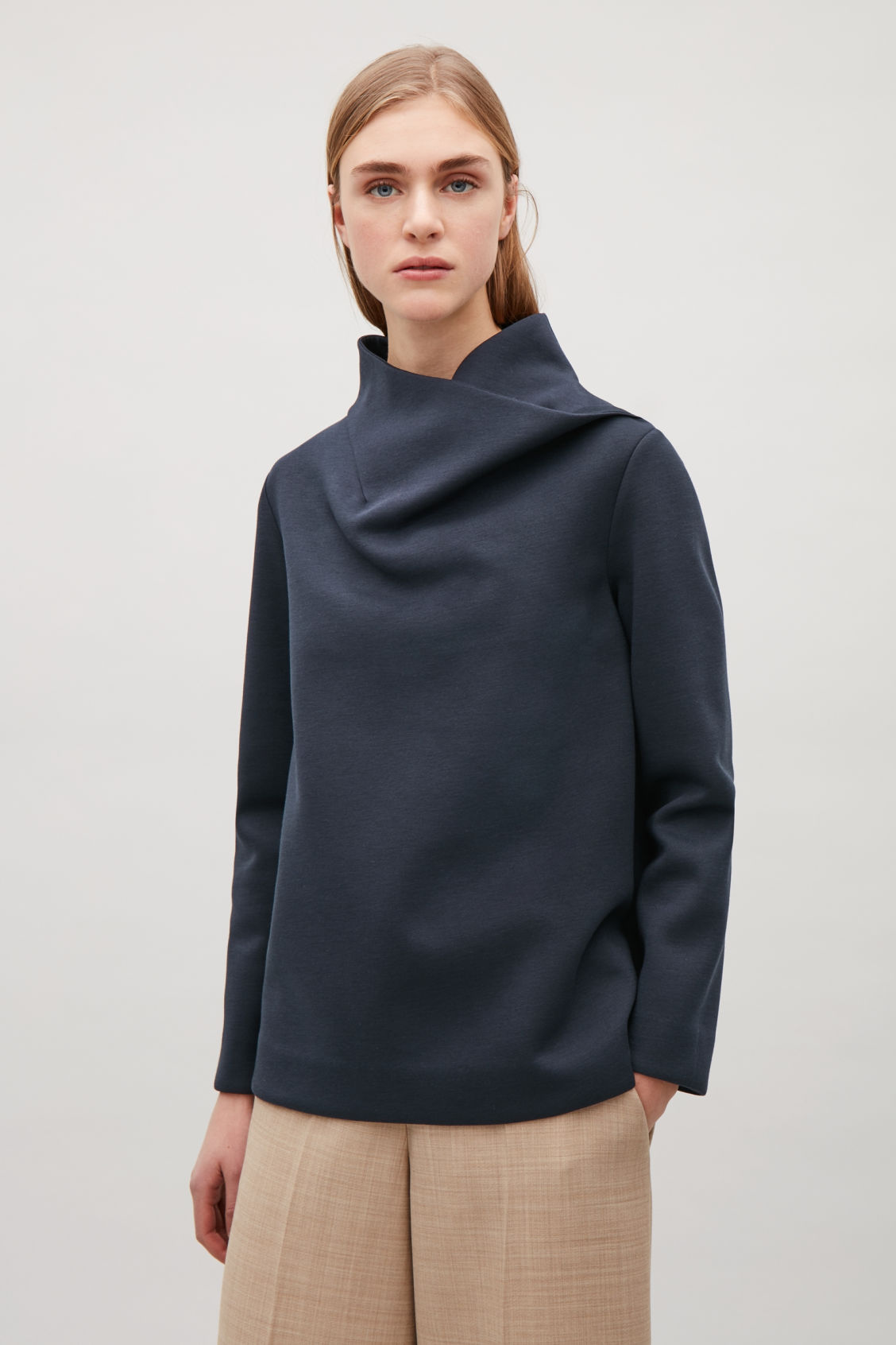 Model side image of Cos top with draped neck in blue