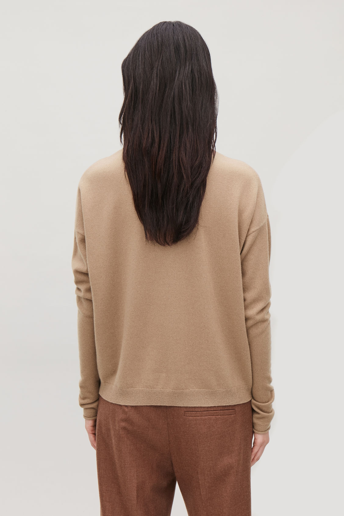 Model side image of Cos roll-neck cashmere jumper in beige