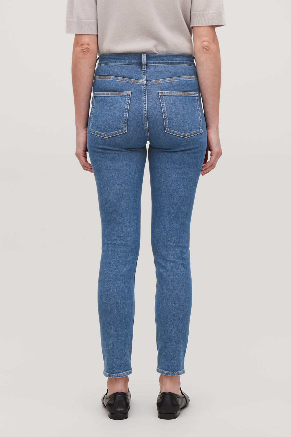 Model side image of Cos cropped skinny-fit jeans in blue