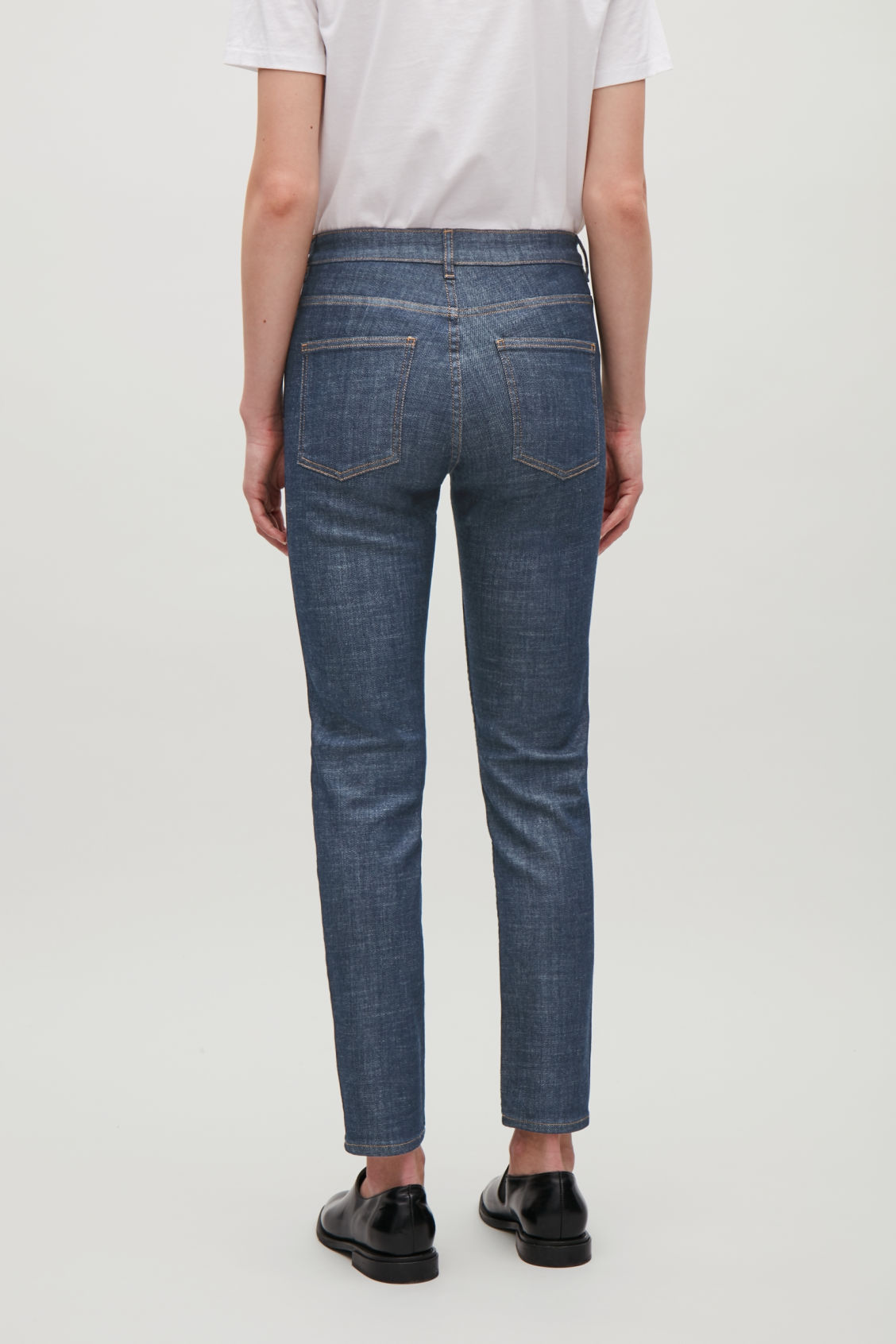 Model side image of Cos skinny-fit cropped jeans in blue
