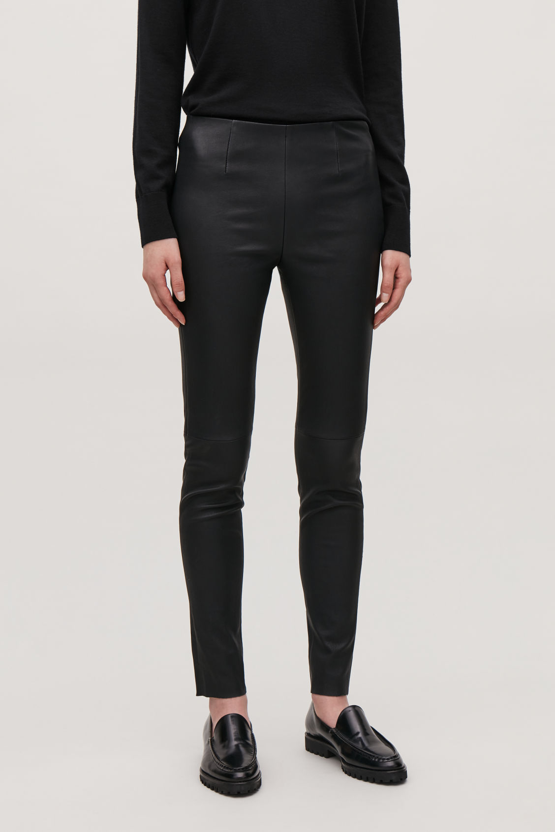 Model side image of Cos slim-fit leather trousers in black
