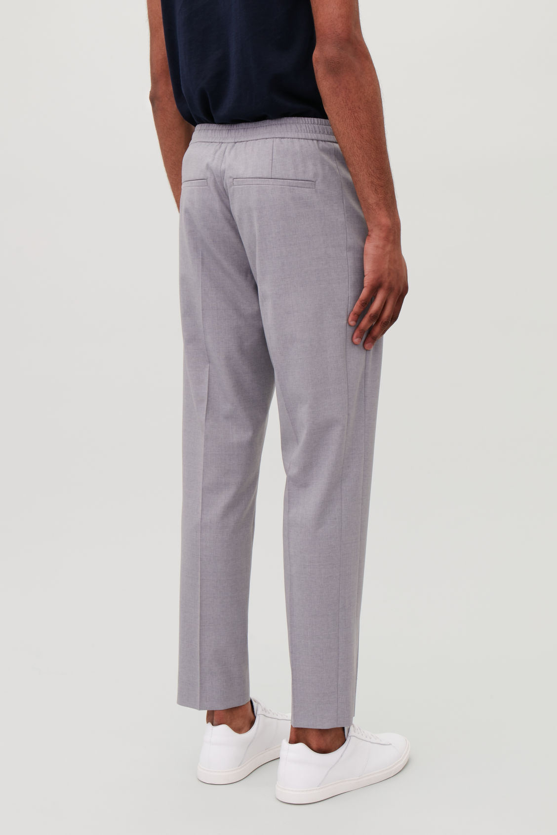 Model side image of Cos slim-fit trousers with elastic waist in grey
