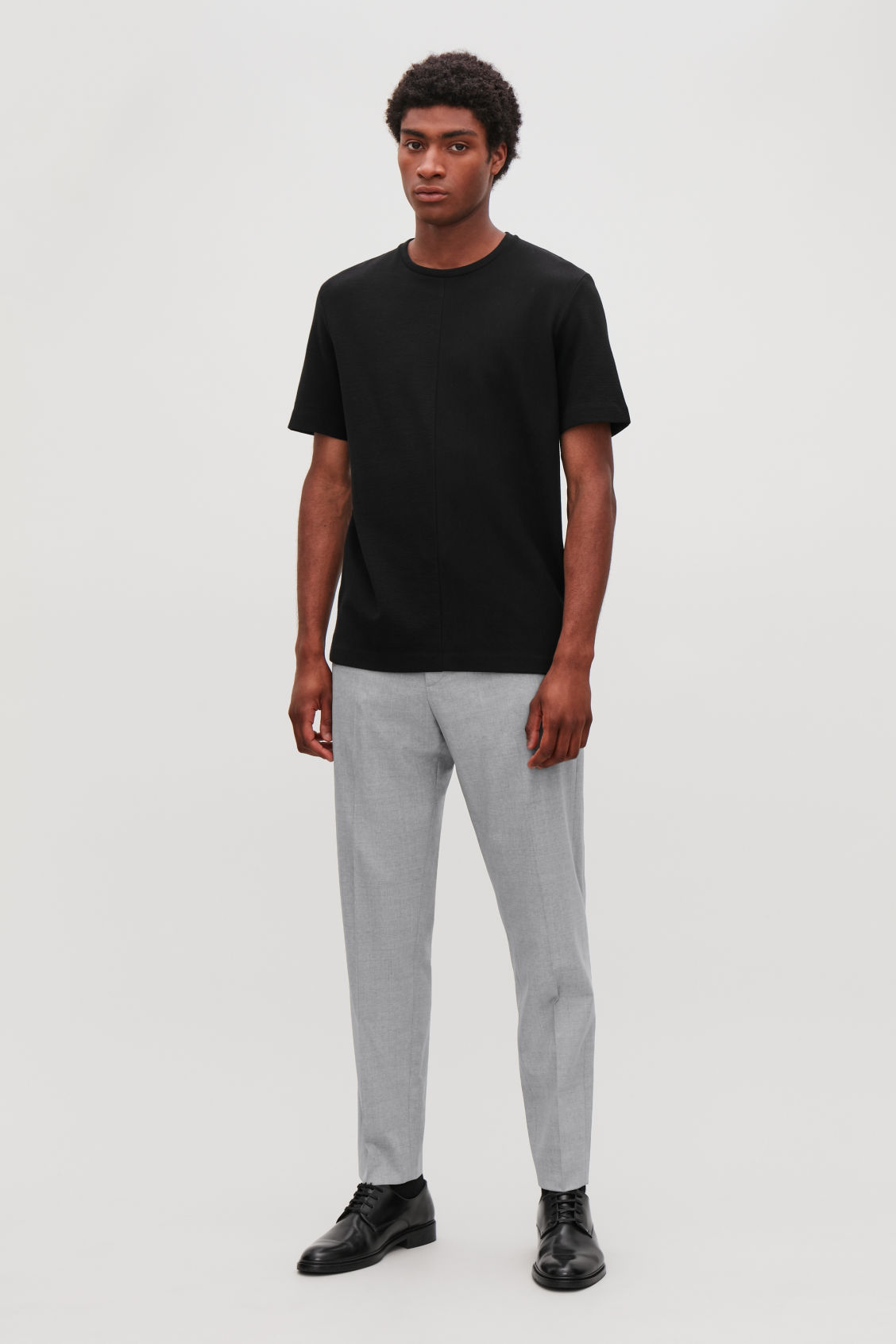 Model side image of Cos elasticated slim-fit trousers in grey