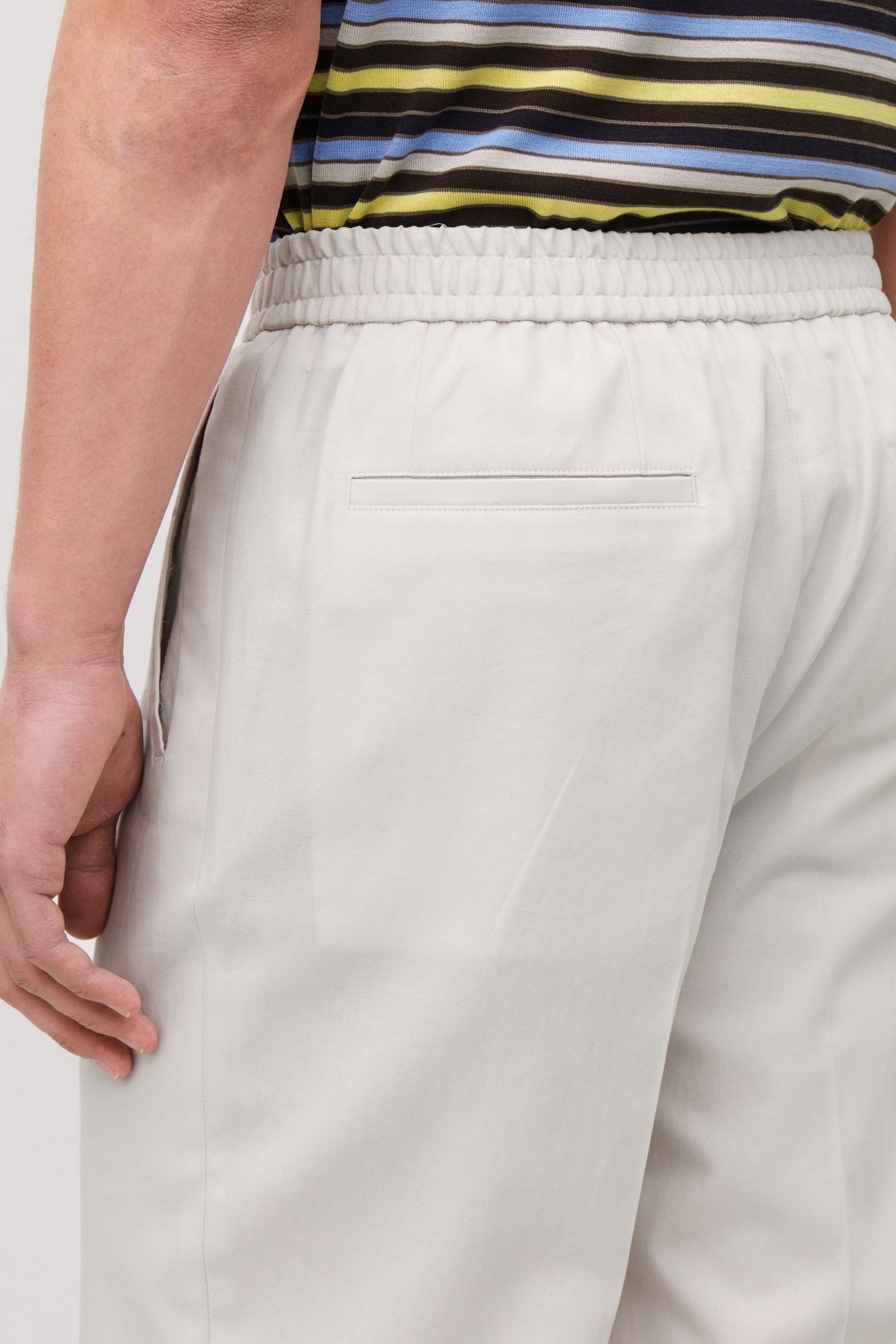 Model side image of Cos relaxed turn-up trousers in beige