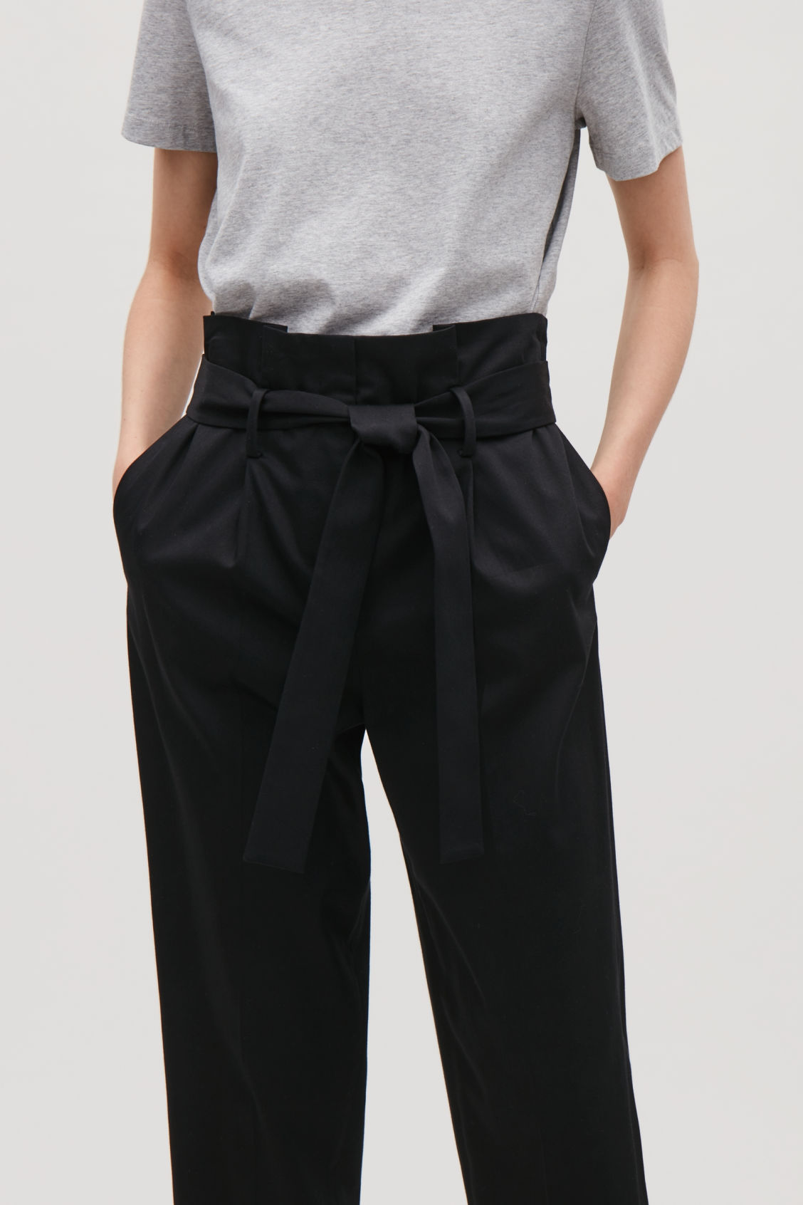 Model side image of Cos trousers with waist tie in black