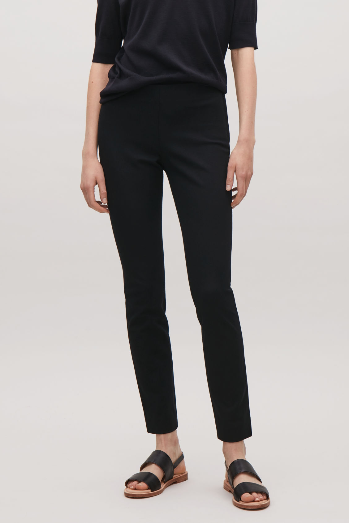 Model side image of Cos slim-fit trousers in black