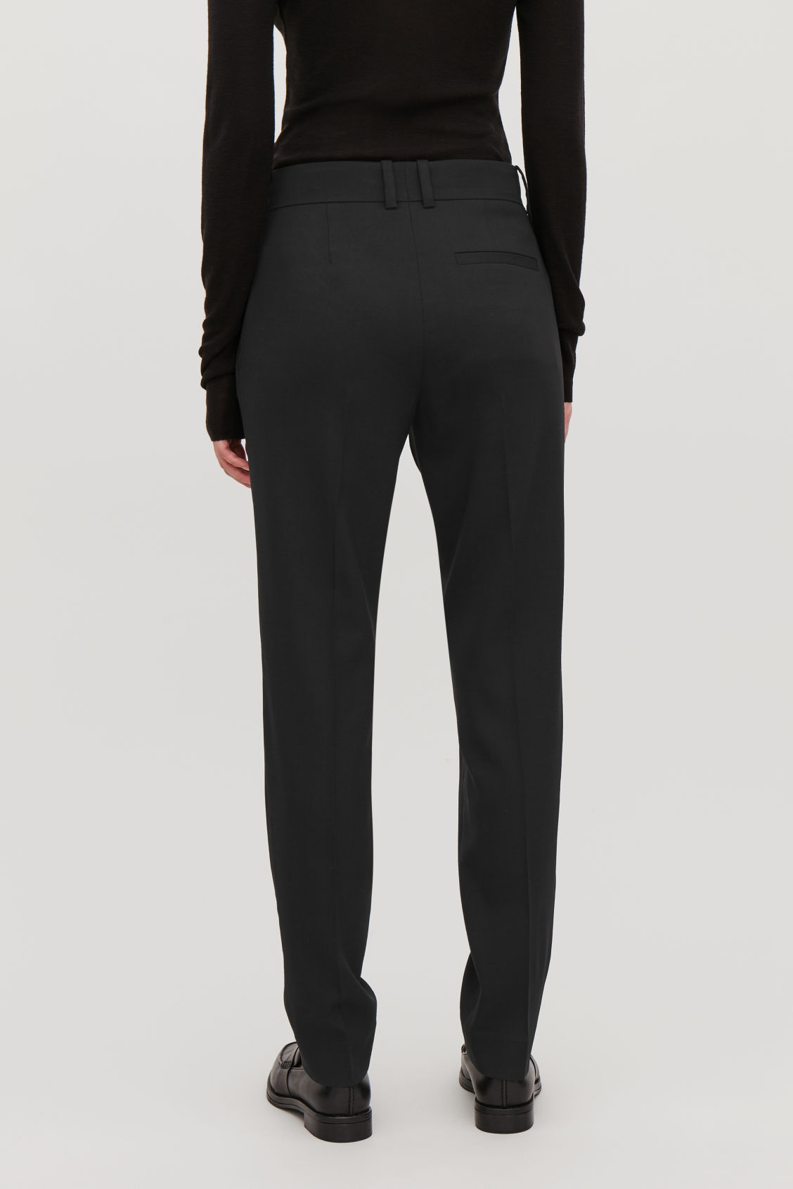 Model side image of Cos tailored wool trousers in black