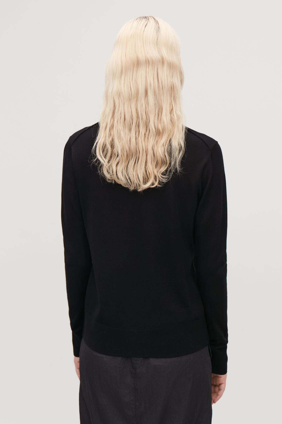 Model side image of Cos round-neck merino jumper in black