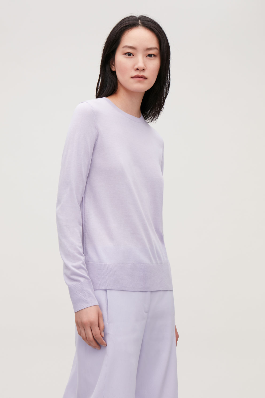 Model side image of Cos round-neck merino jumper in purple
