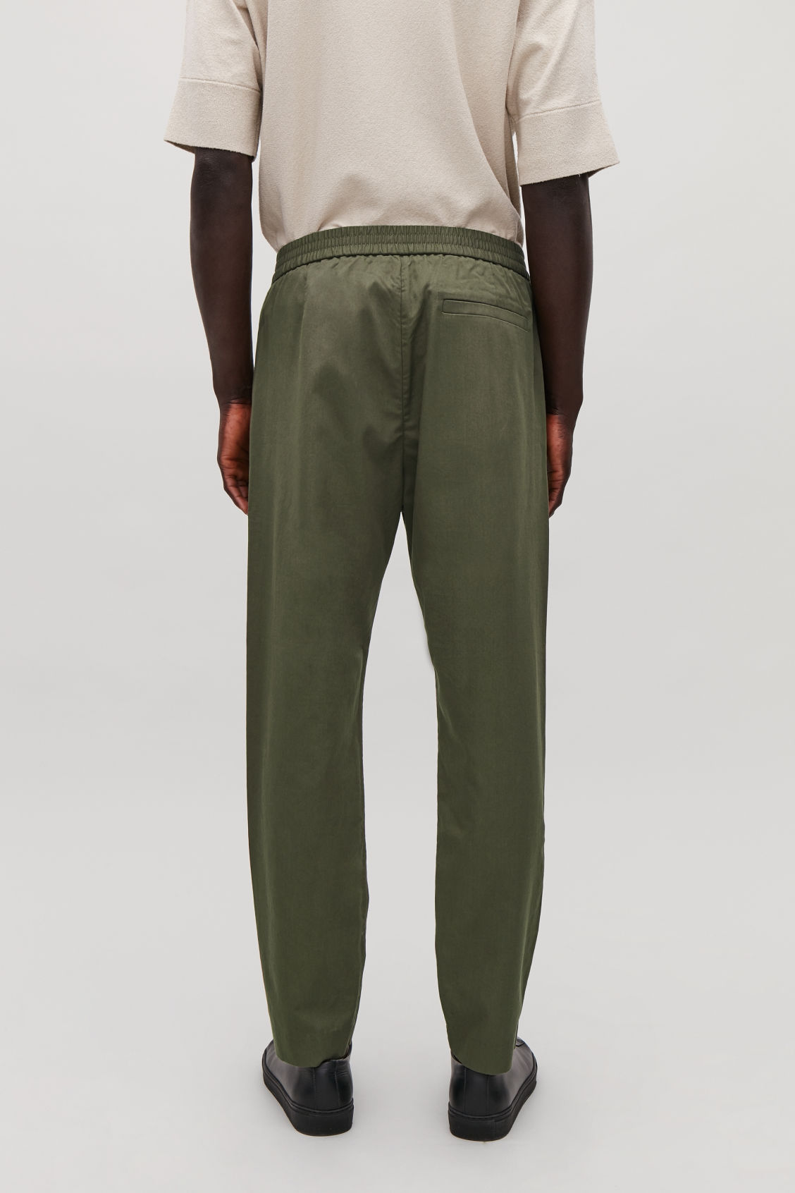 Model side image of Cos tailored trousers with elastic waist in green