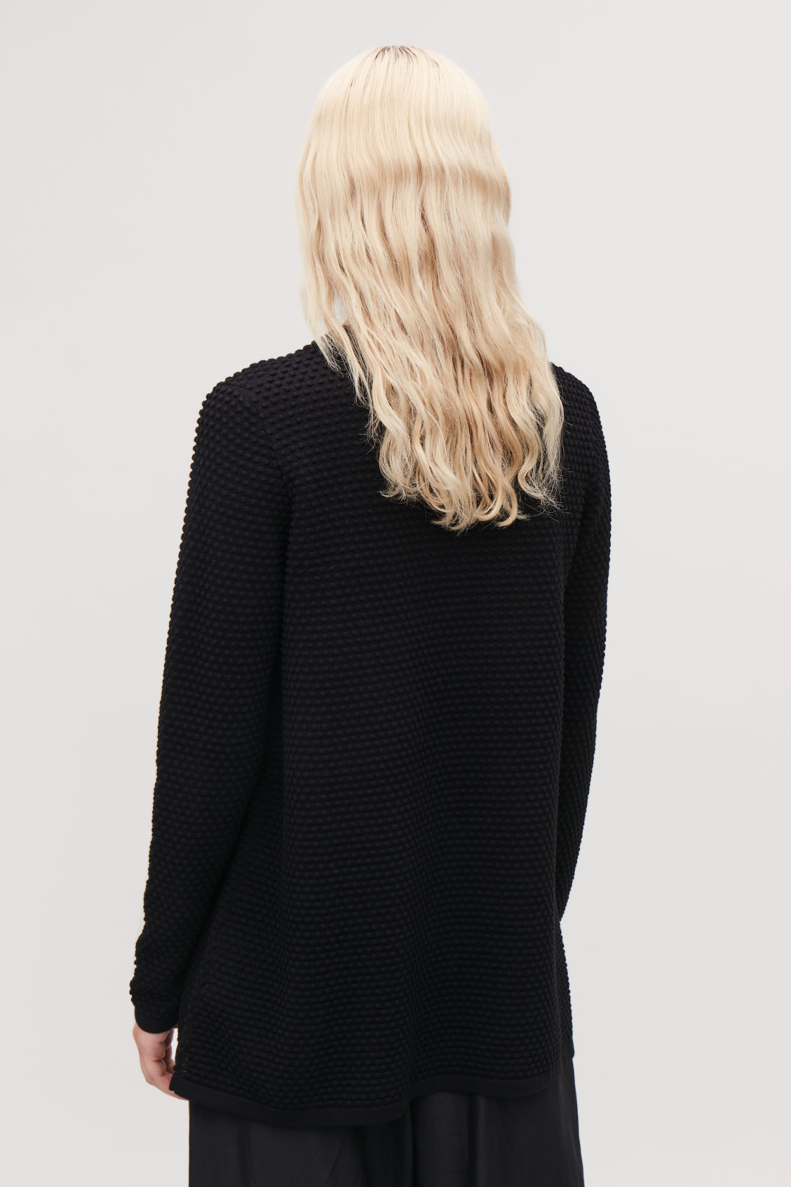 Model side image of Cos textured a-line top in black