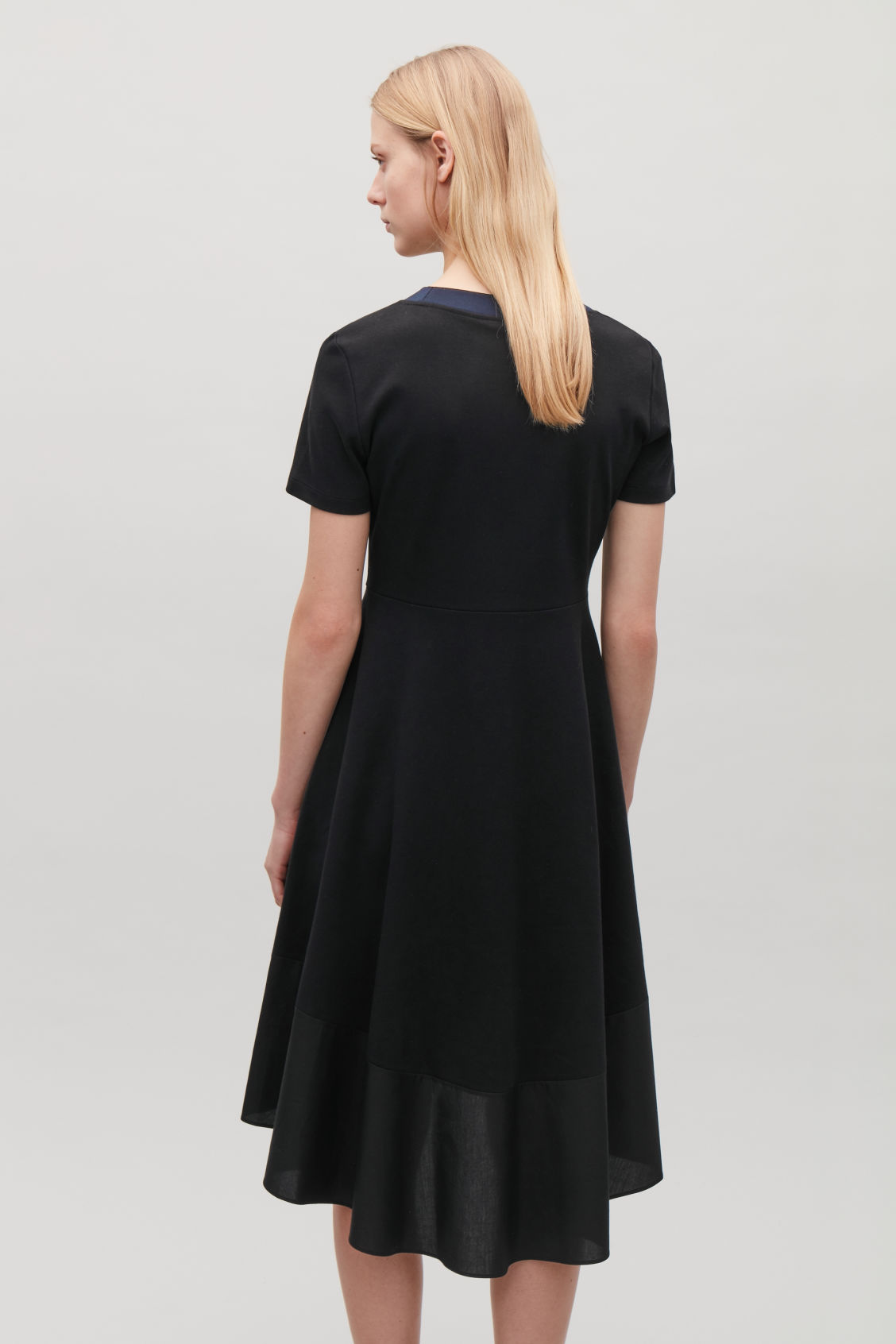 Model side image of Cos panelled jersey dress in black