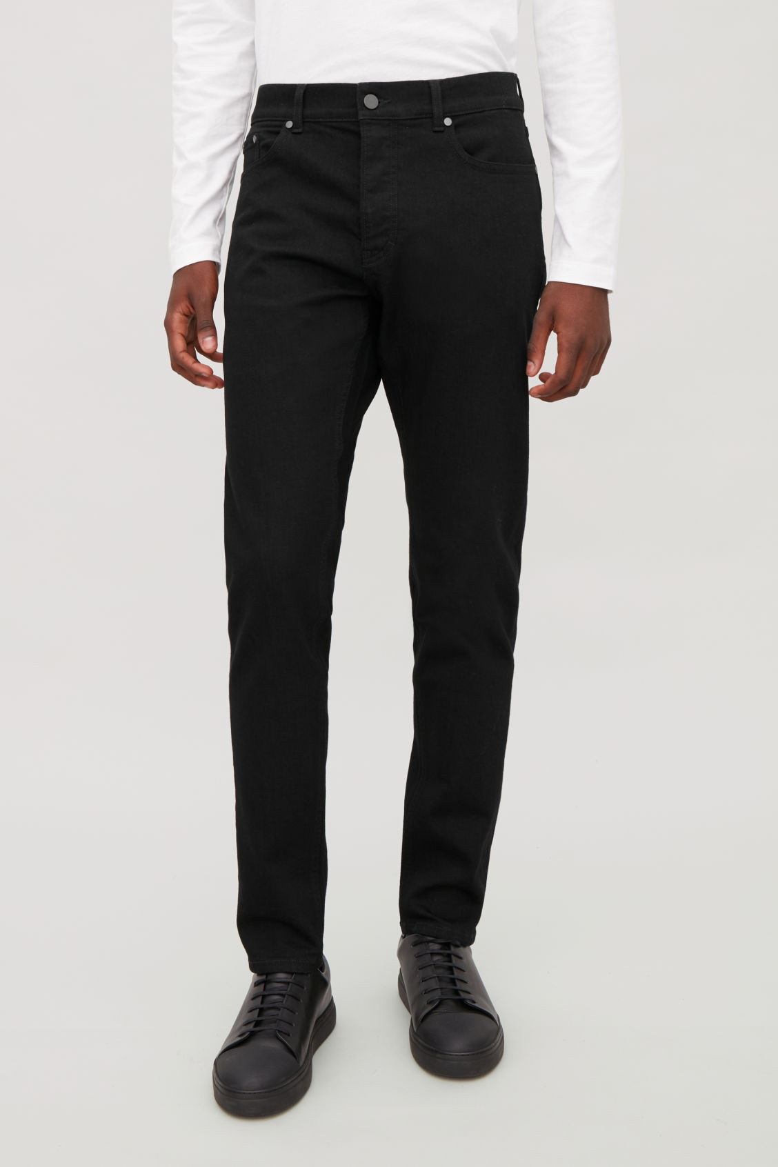 Model side image of Cos slim tapered jeans in black