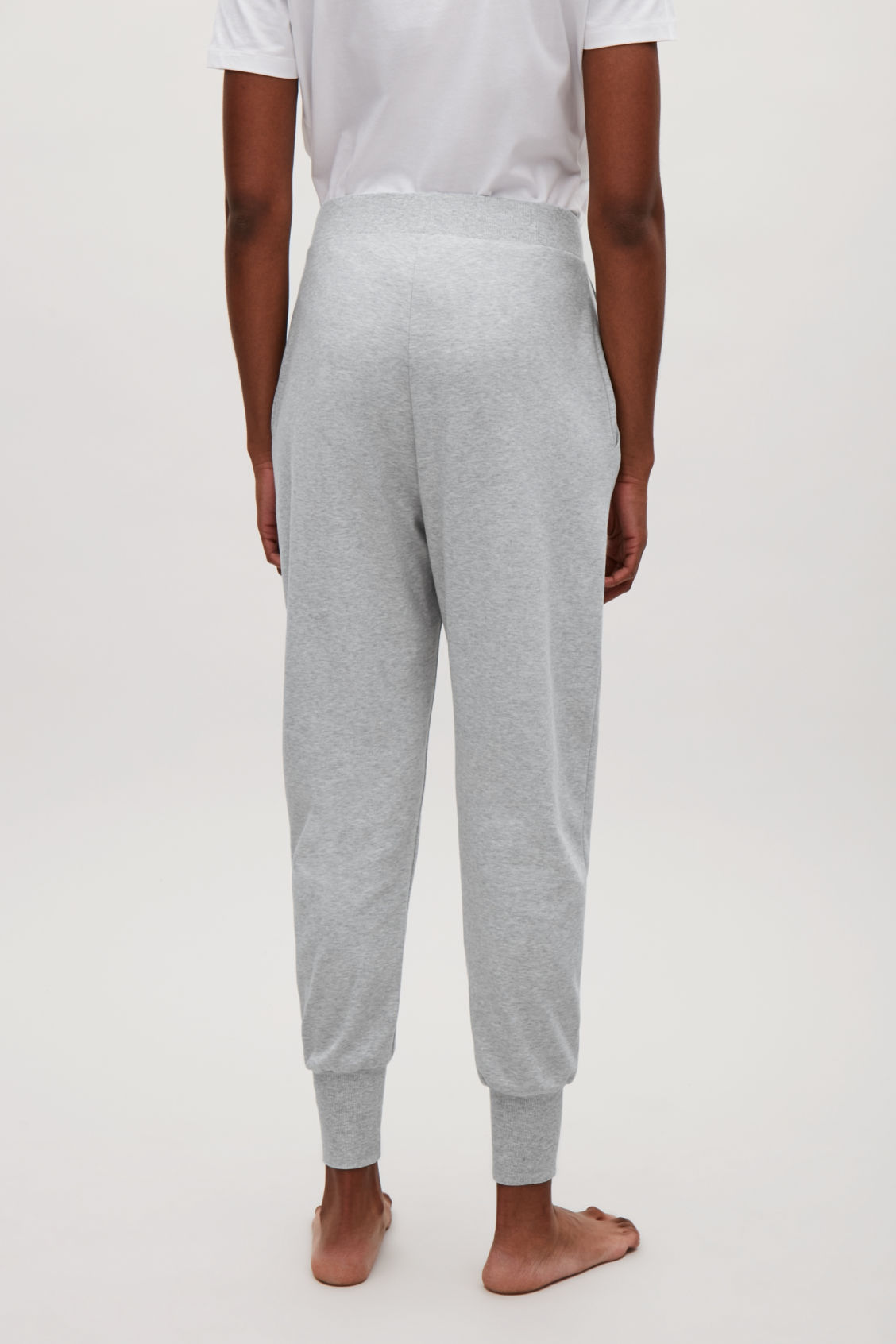 Model side image of Cos tapered jersey trousers in grey