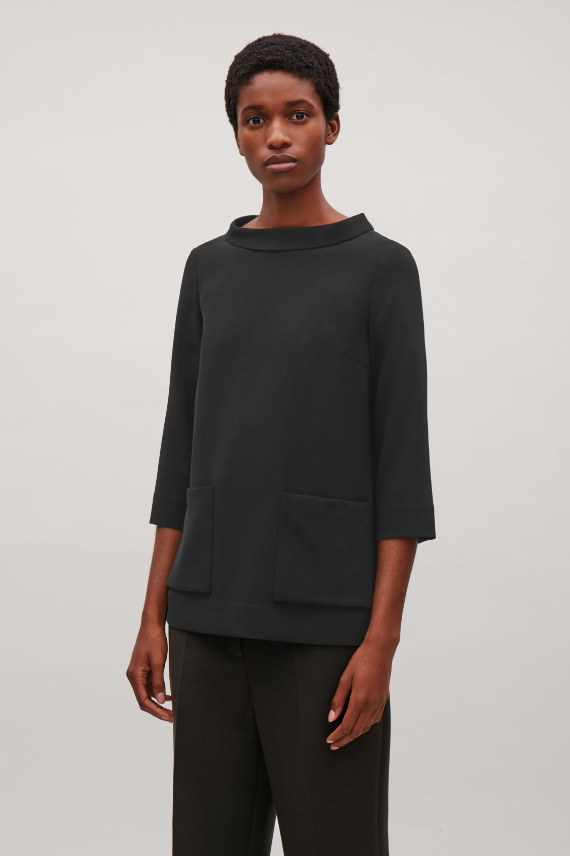 Model side image of Cos top with folded collar  in black