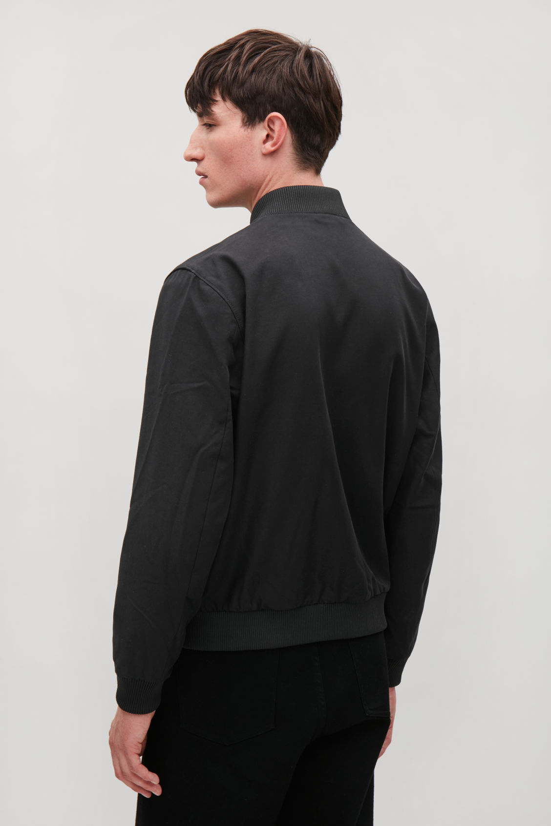 Model side image of Cos bomber jacket with zipped pockets  in black