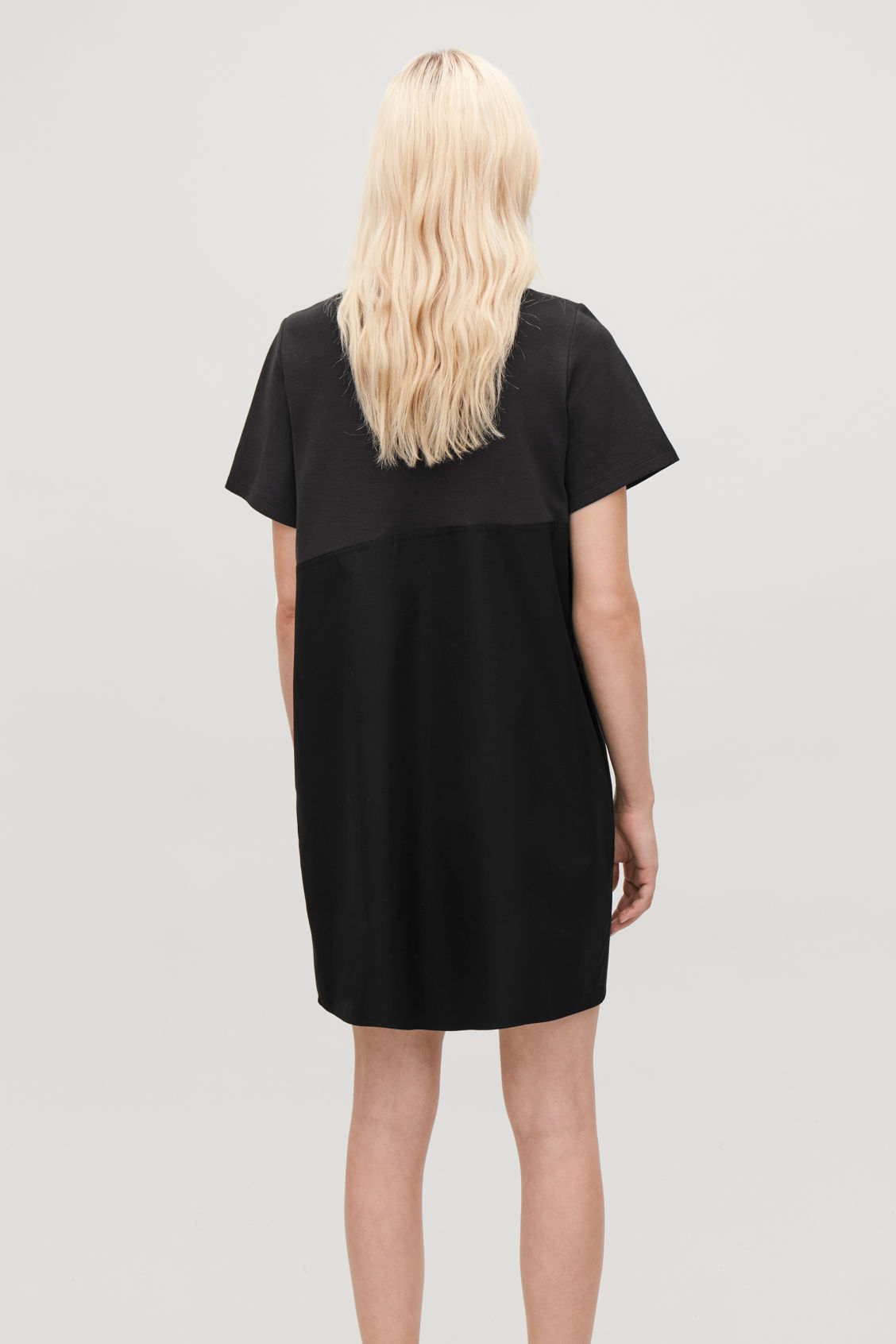 Model side image of Cos dress with overlap front in black