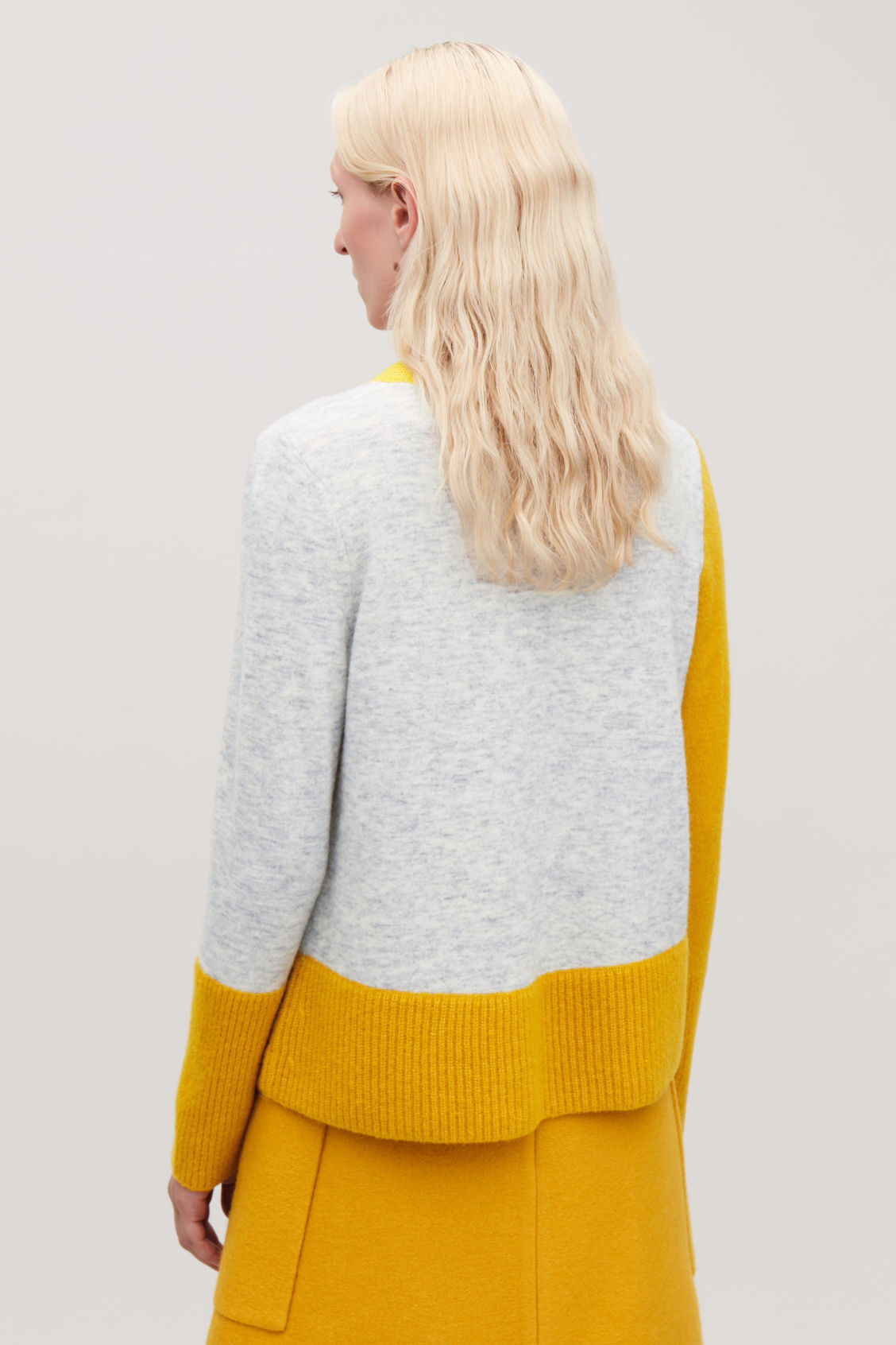 Model side image of Cos colour-block jumper with pocket in yellow