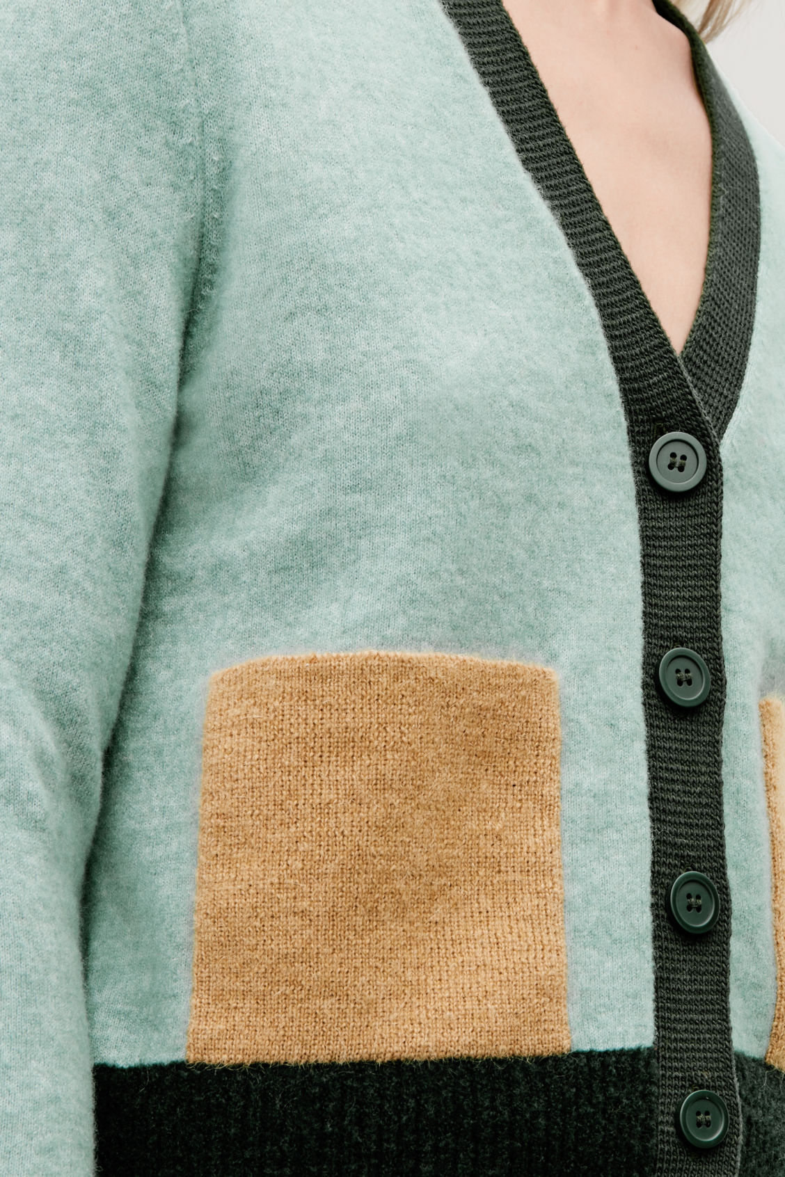 Model side image of Cos colour-block cardigan with pockets in green