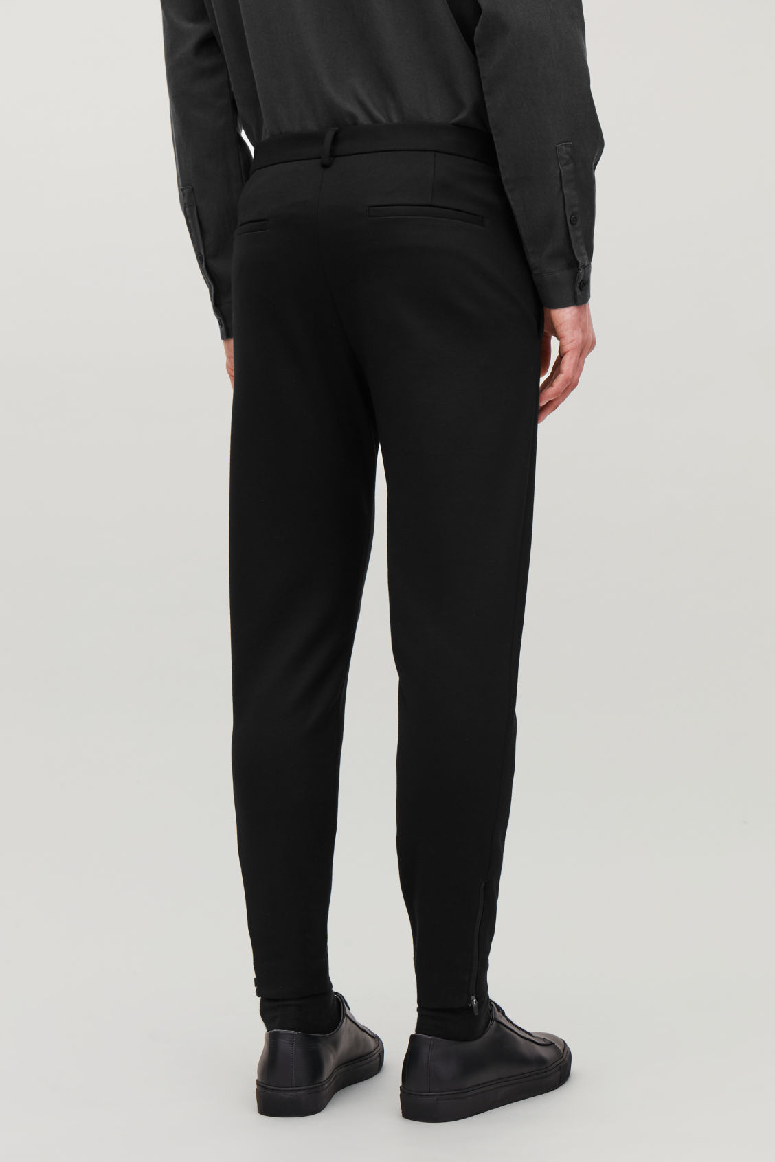 Model side image of Cos zip-cuff jersey trousers in black