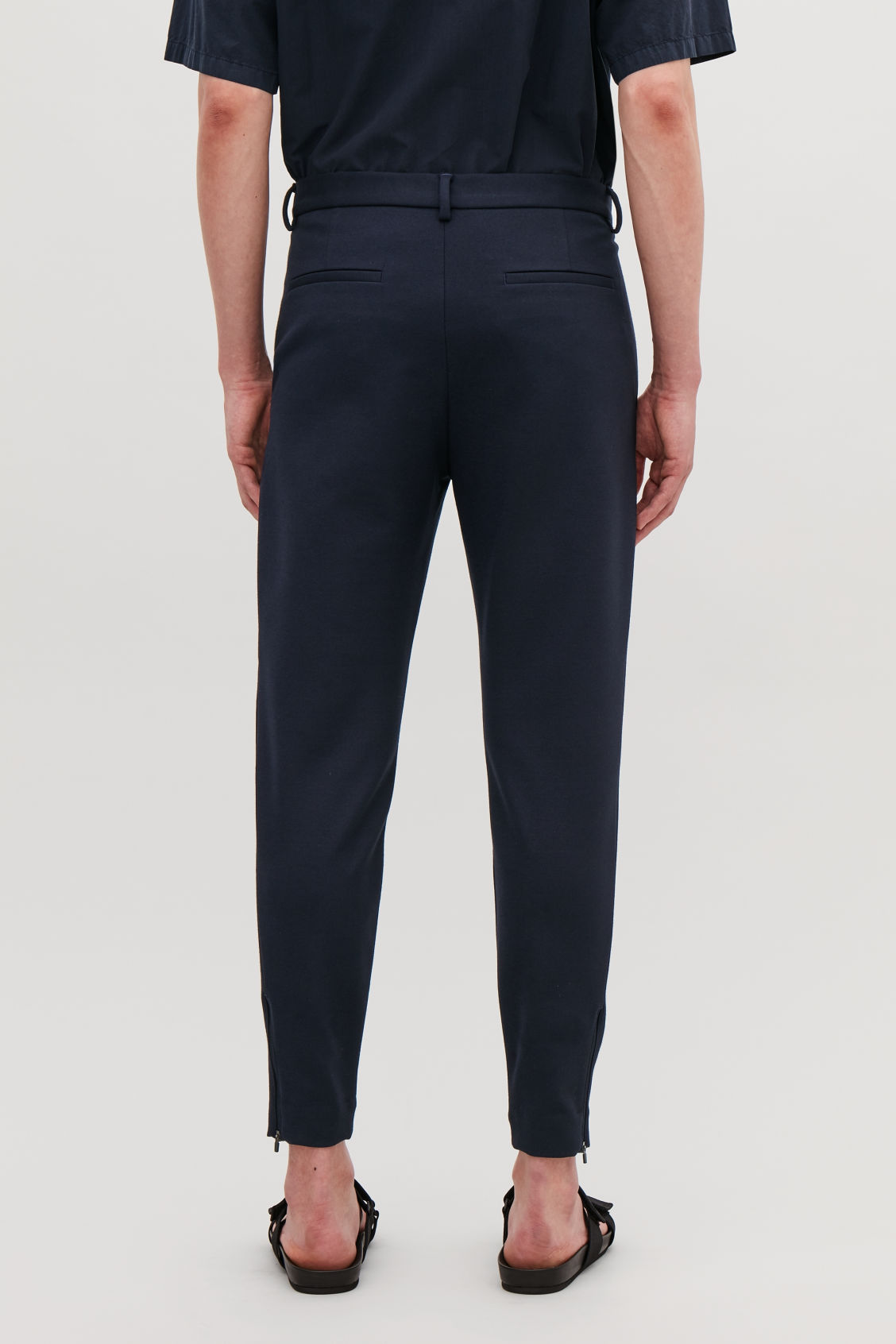 Model side image of Cos zip-cuff jersey trousers in blue