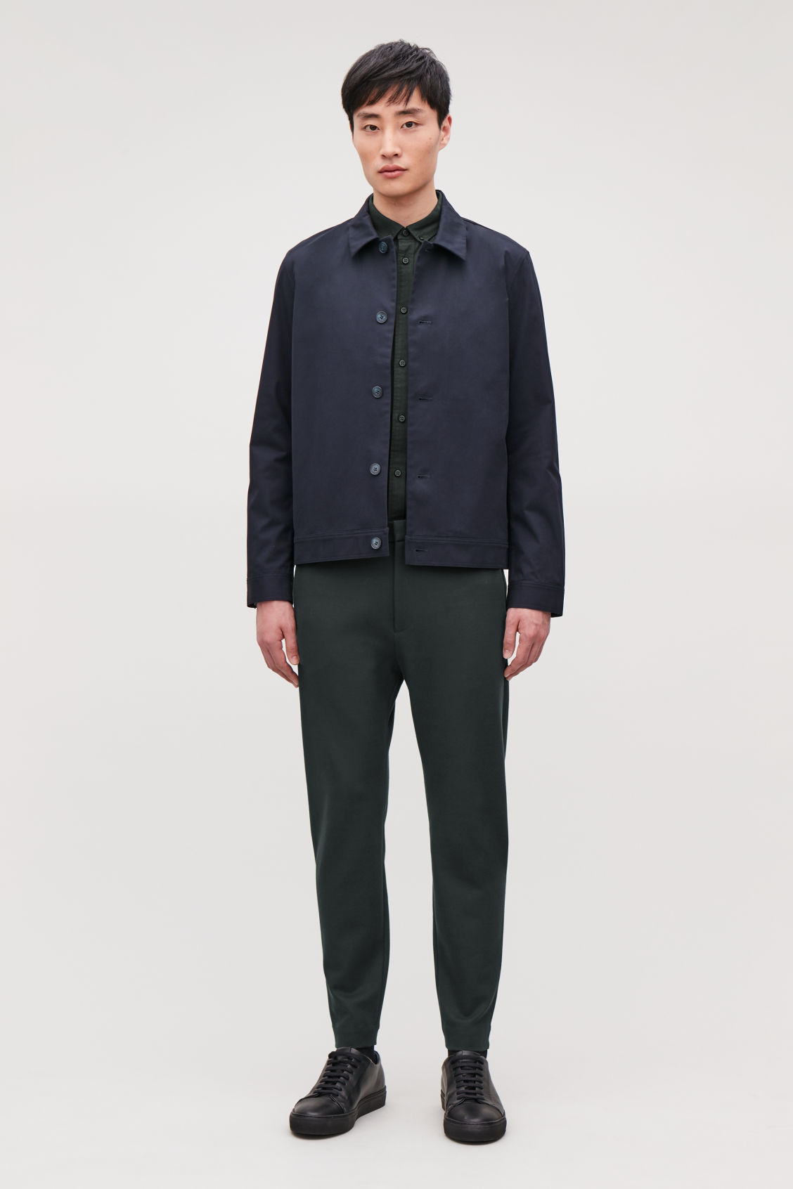 Model side image of Cos zip-cuff jersey trousers in green