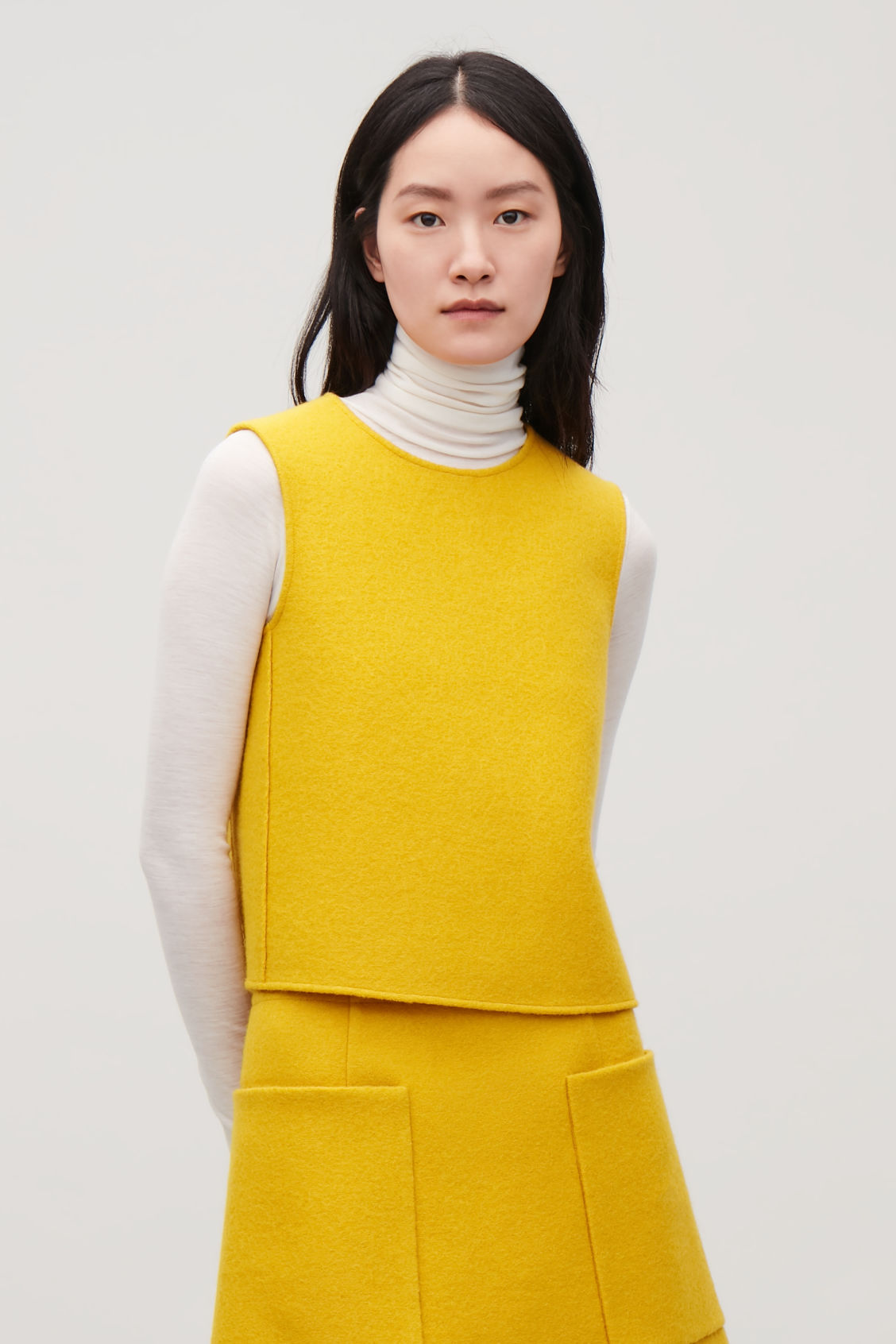 Model side image of Cos panelled wool vest top  in yellow