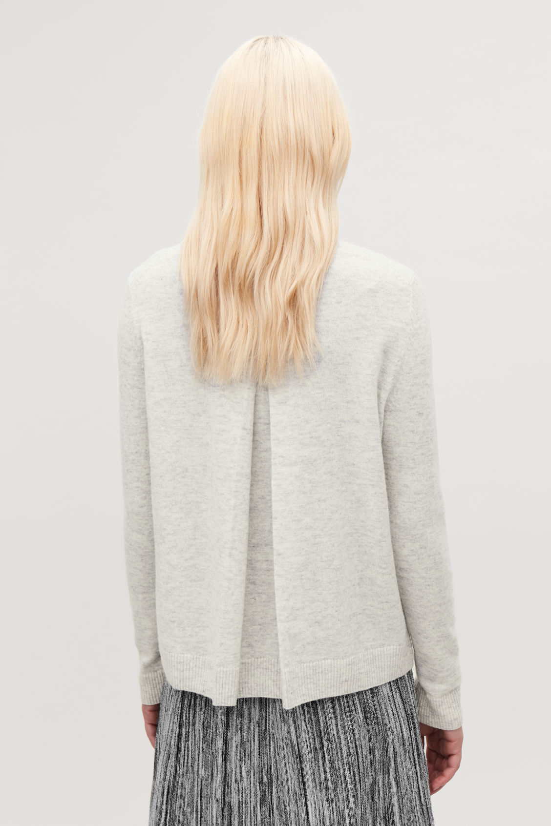 Model side image of Cos lambswool cardigan with back pleat  in grey