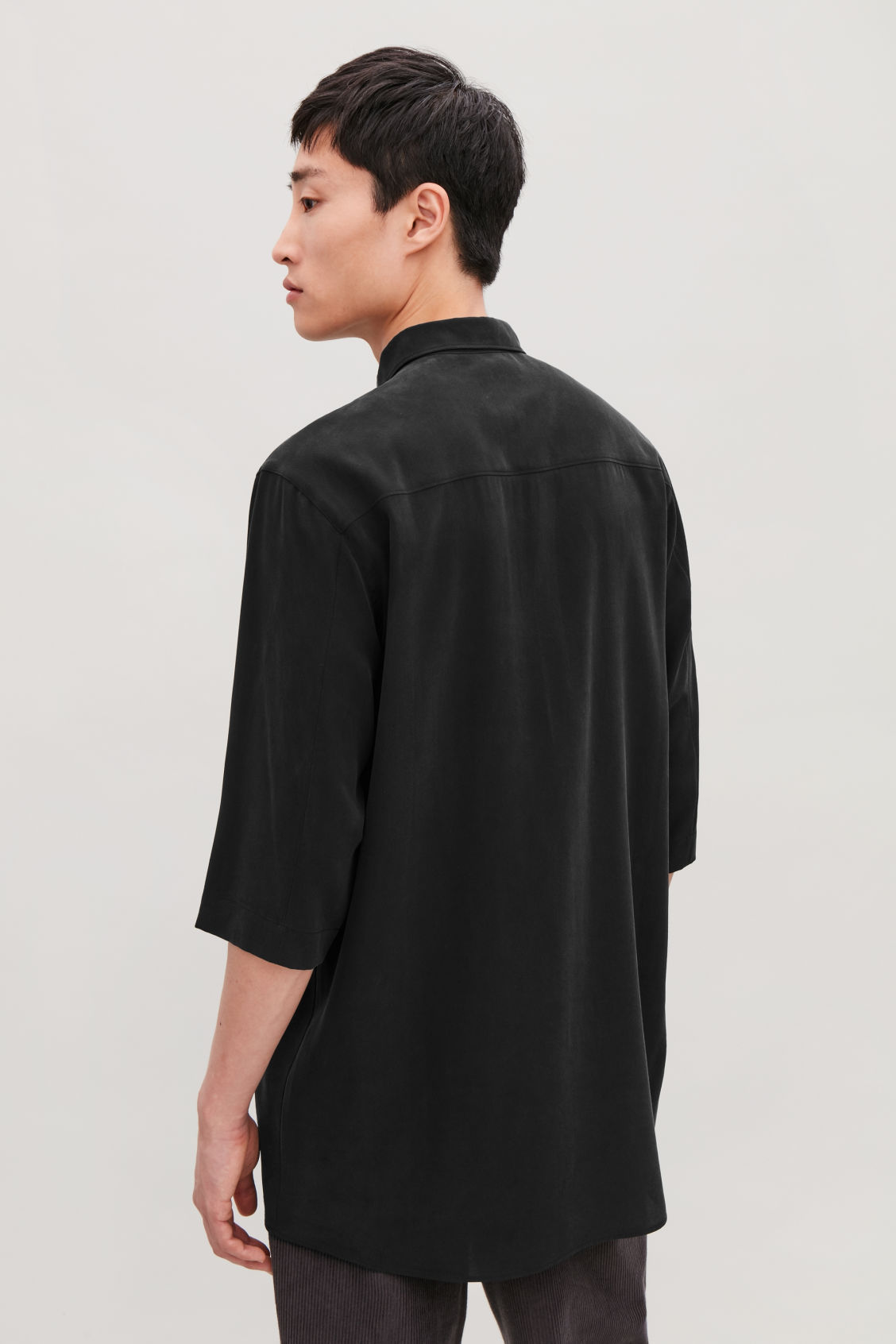 Model side image of Cos silk shirt with ¾ sleeves in black