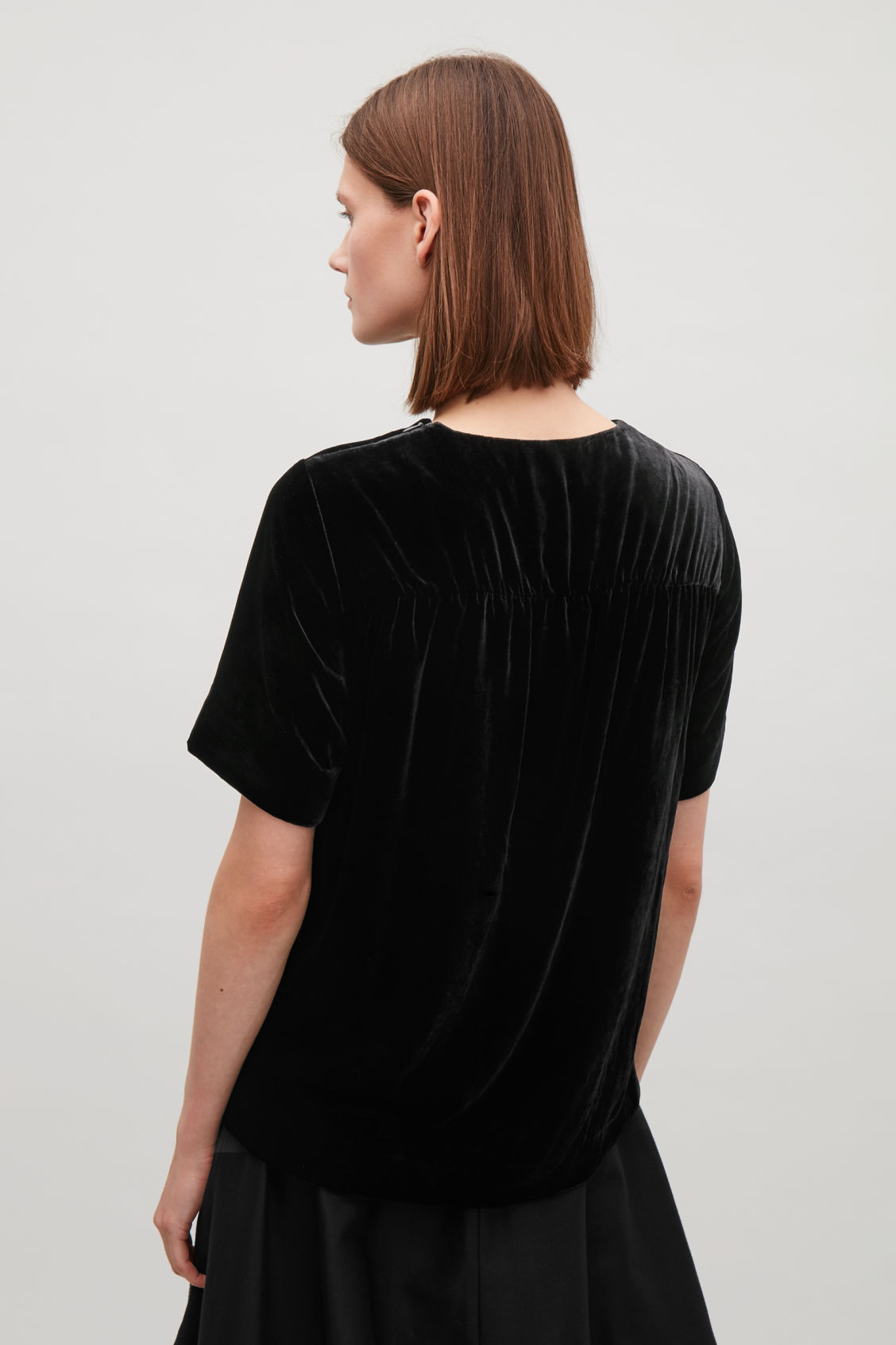 Model side image of Cos velvet top with back detail in black