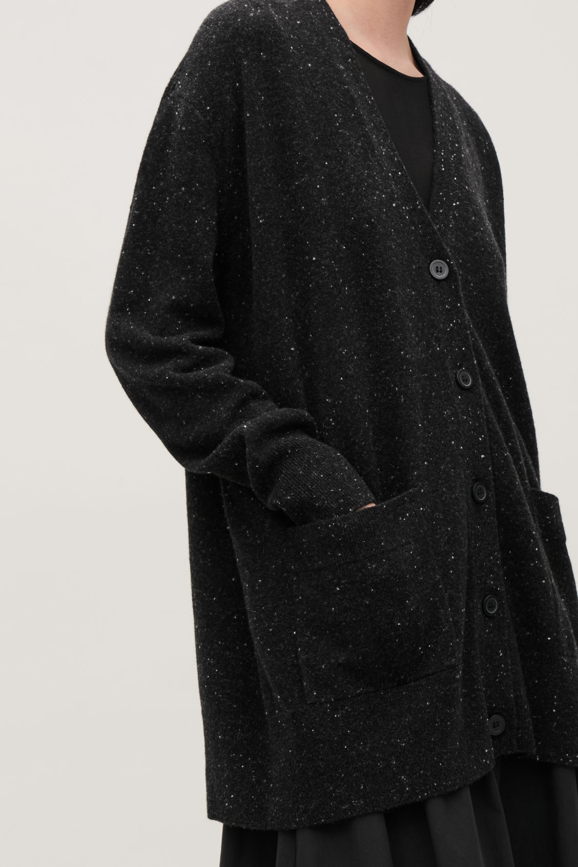 Model side image of Cos speckled oversized wool cardigan in black