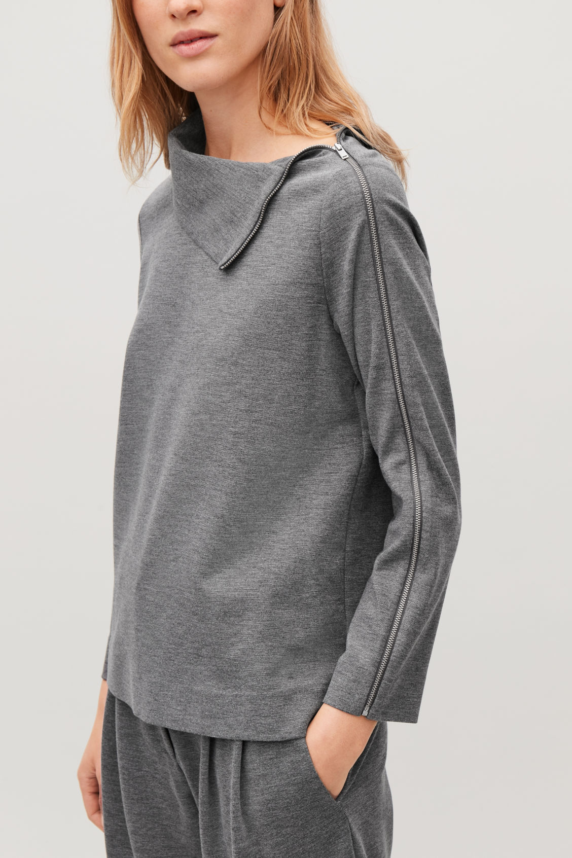 Model side image of Cos jersey top with metal zip in grey