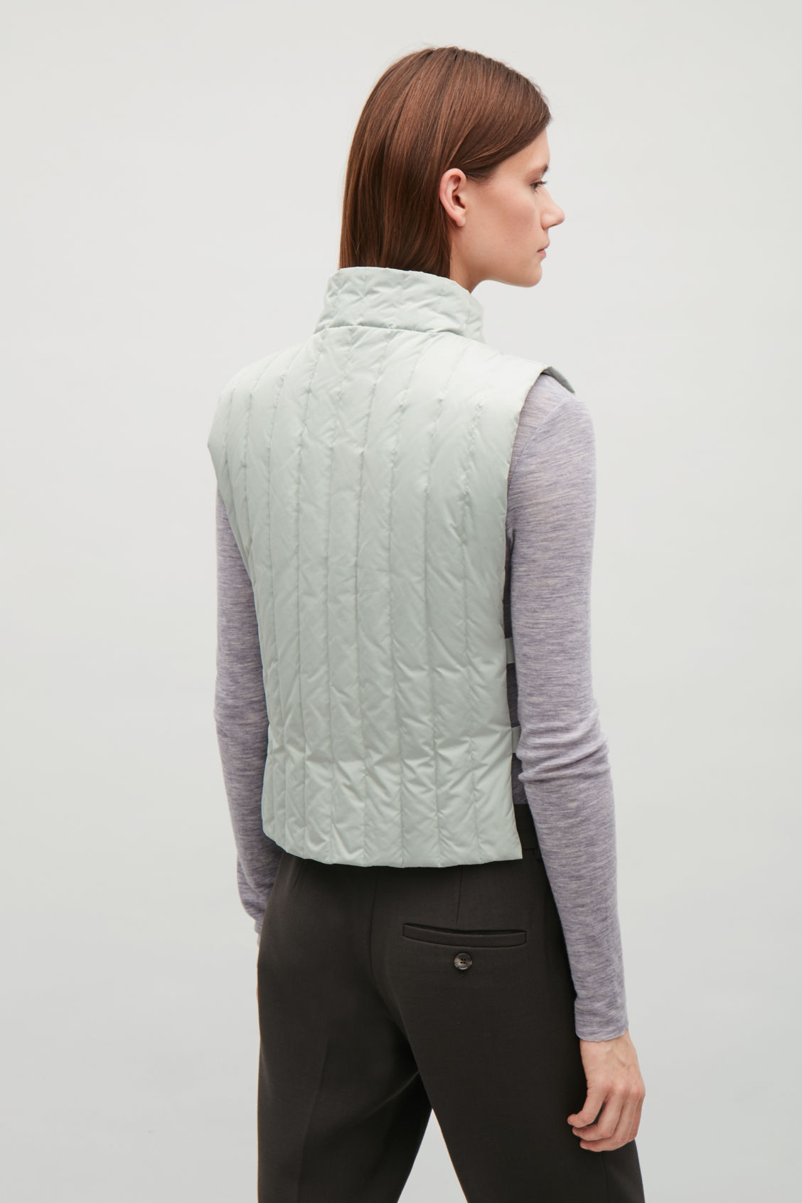 Model side image of Cos padded gilet with elastic detail in green